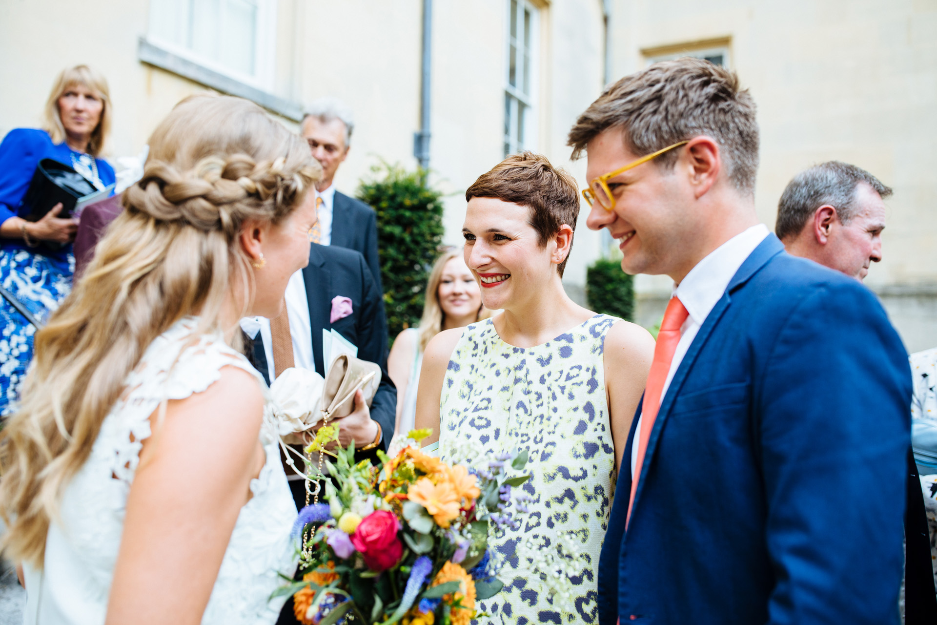 wedding guest in leopard print dress and short brown hair smiling and laughing