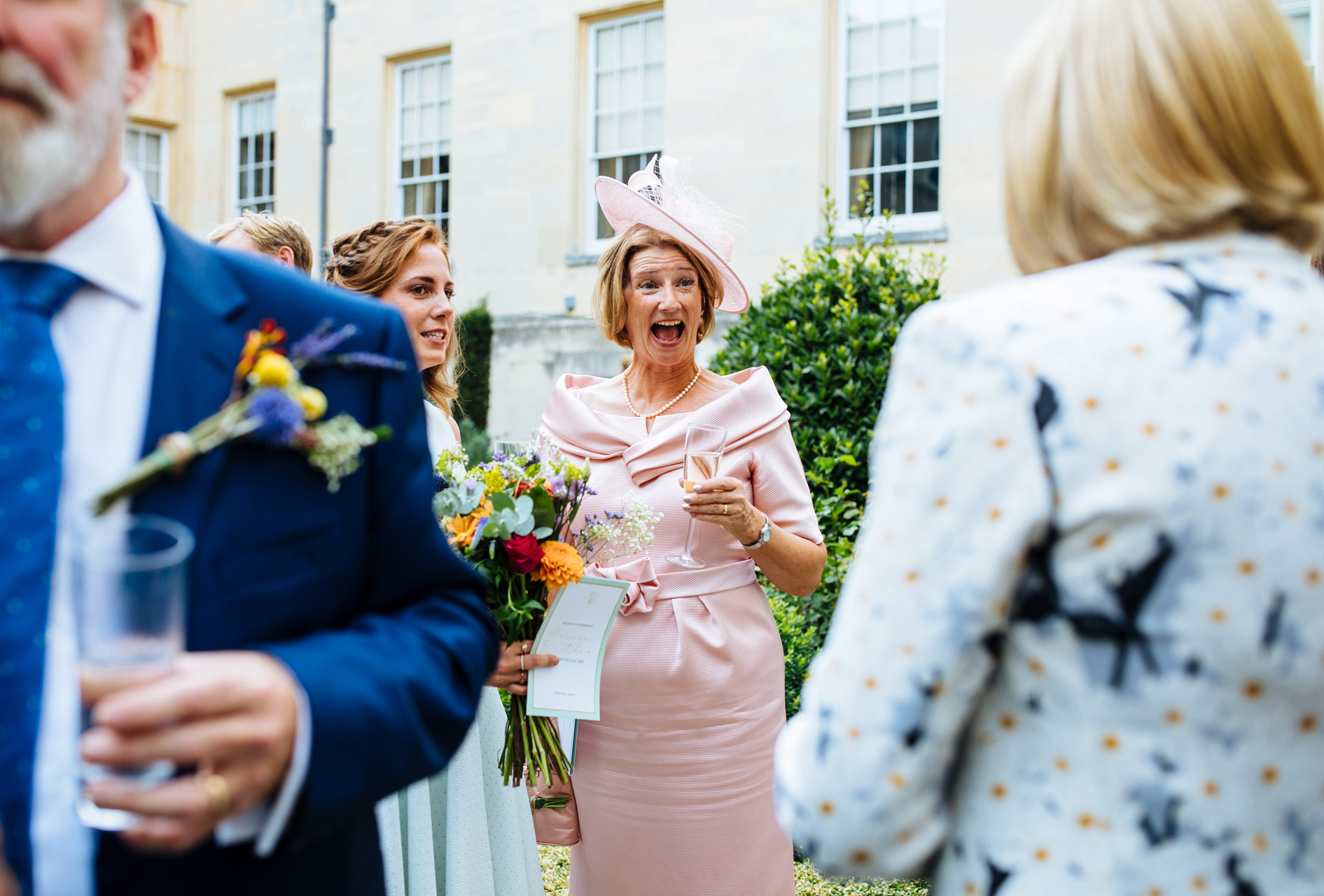 mother of the bride surprised and happy bride and groom saying vows in wedding ceremony in the great hall at syon park