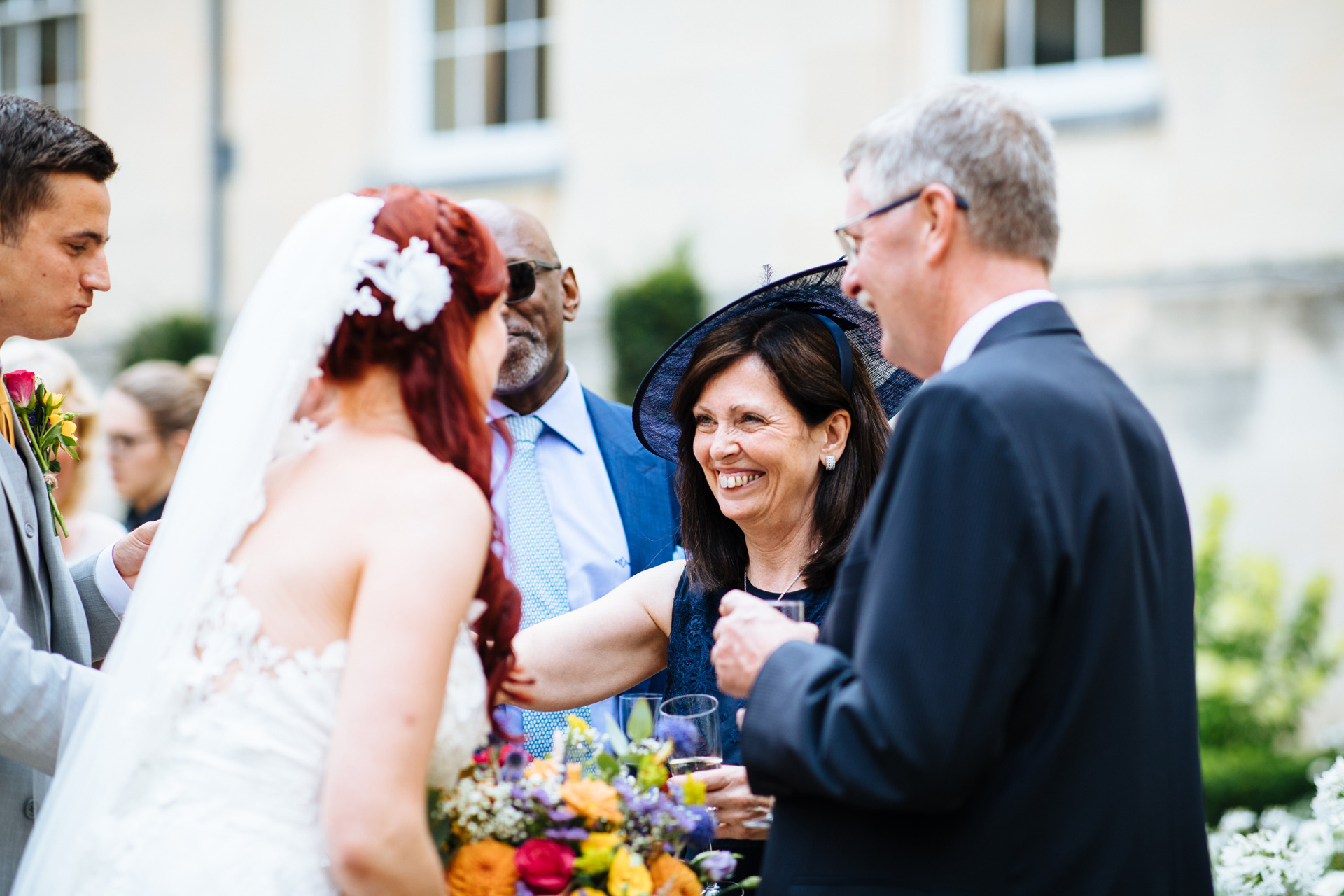 female wedding guest with navy dress and hat smiling at the bride
