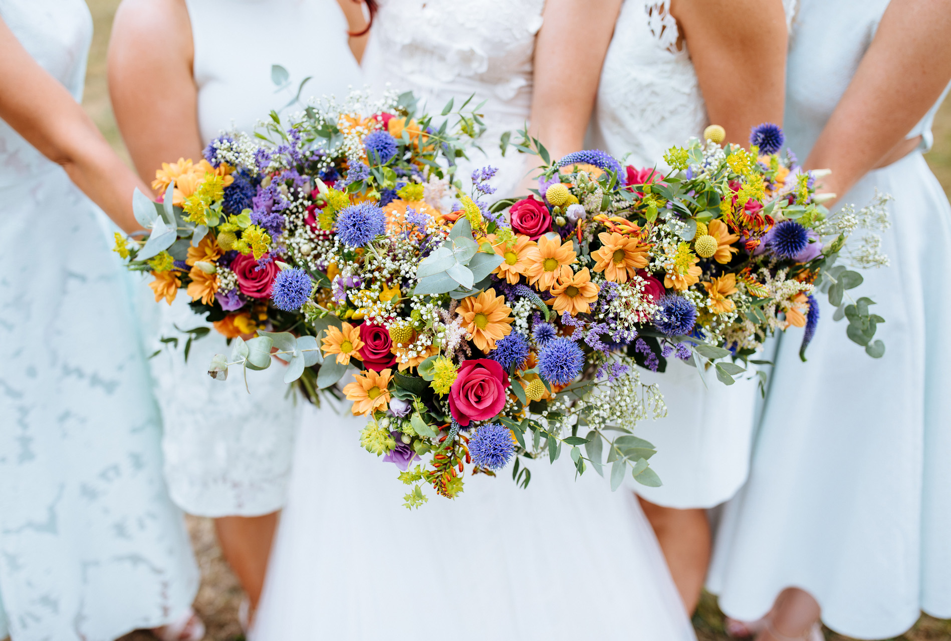 bride and bridesmaids bouquets with purple, yellow and red flowers at syon park