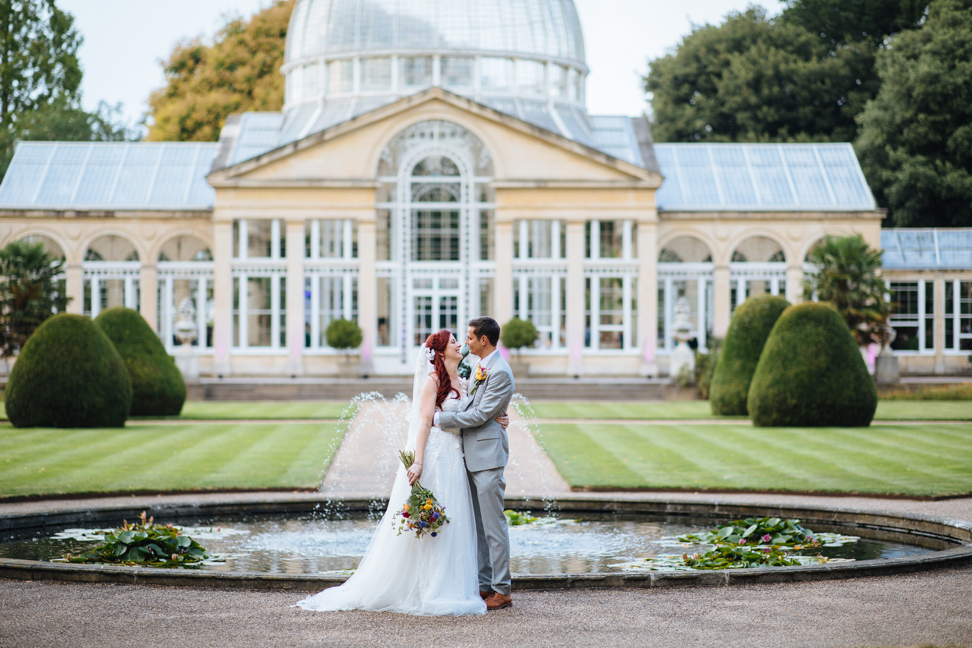 bride and groom cuddling in front of great conservatory at syon park wedding