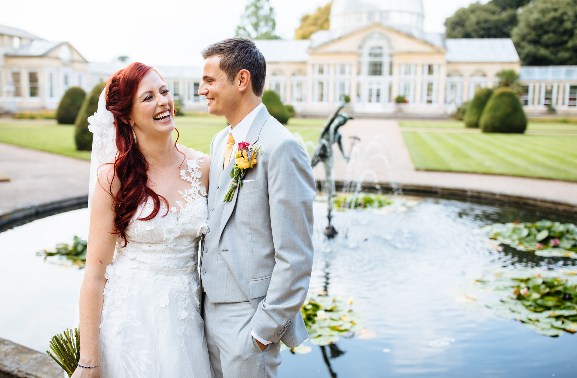 bride and groom laughing in front of great conservatory at Syon park