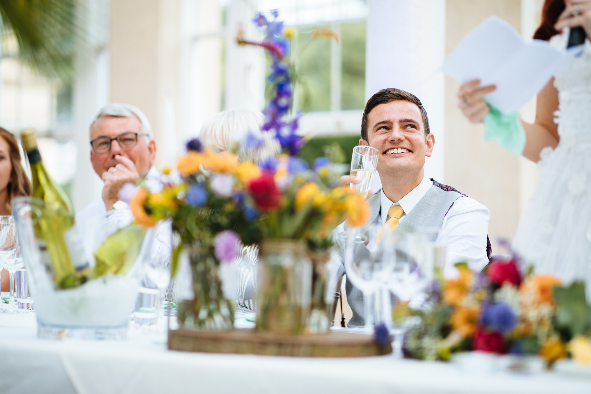 groom smiling at bride and sipping champagne during her speech at syon park wedding