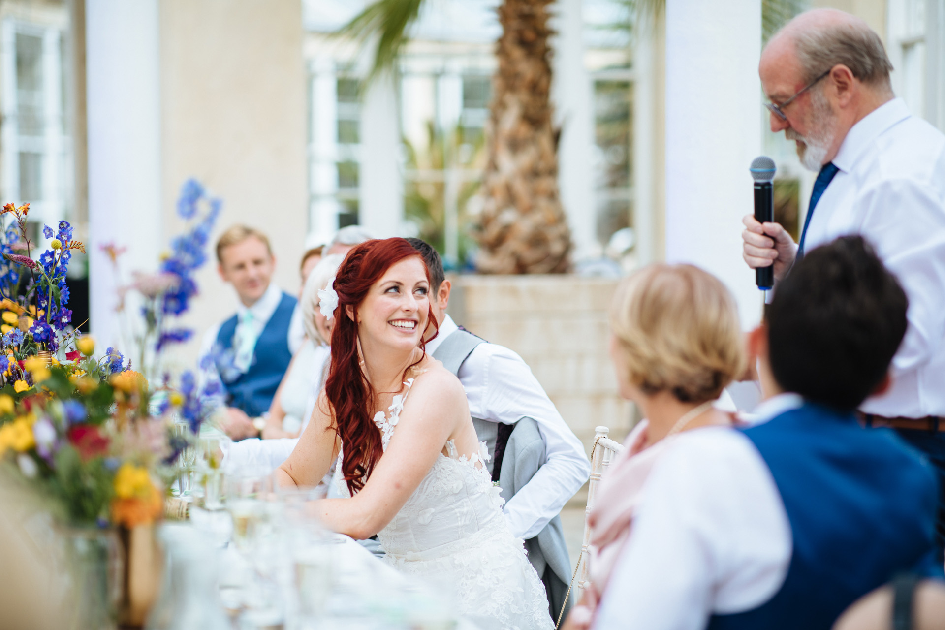 bride turning around and smiling at her father during his speech at syon park