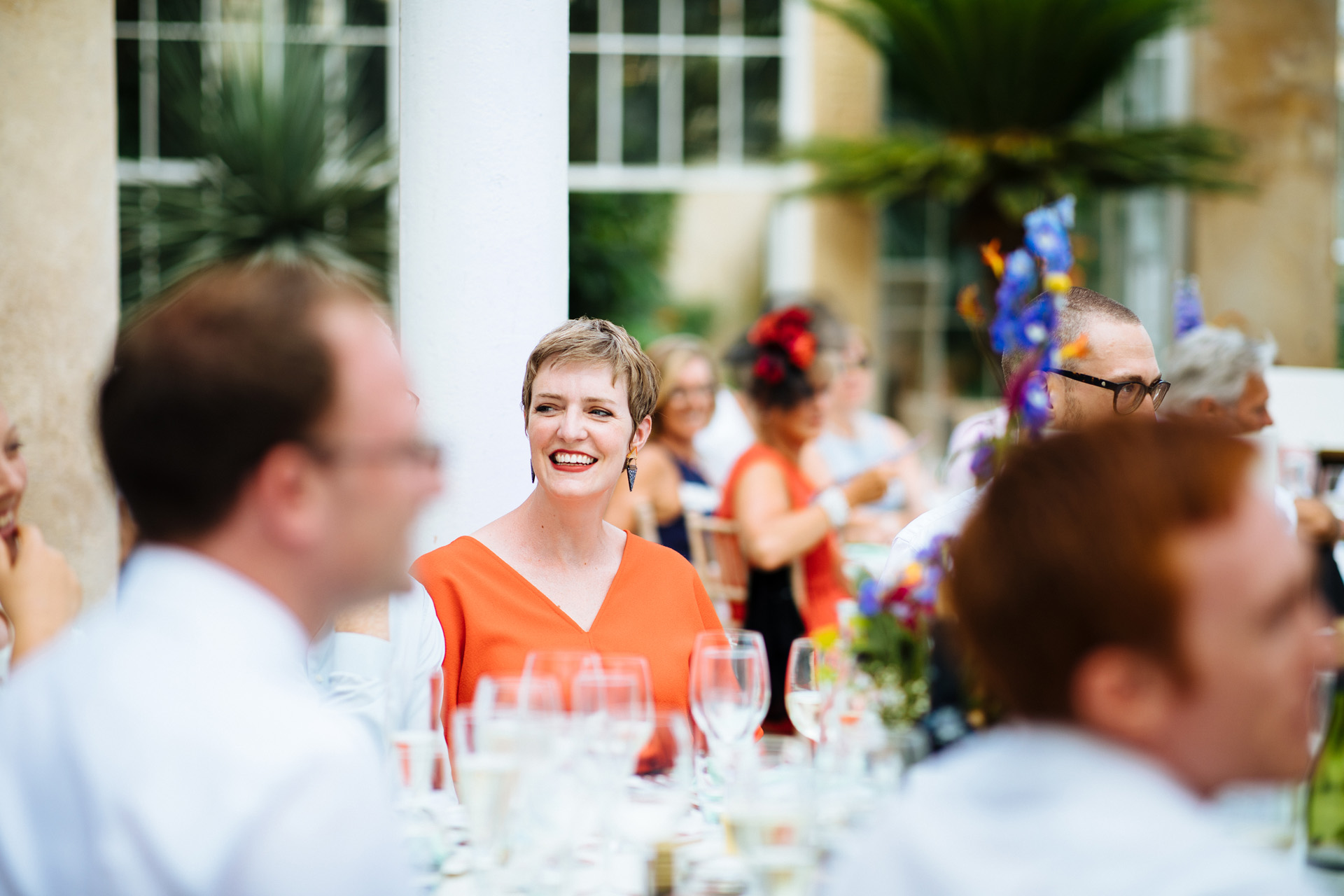 lady in an orange dress smiling at grooms speech