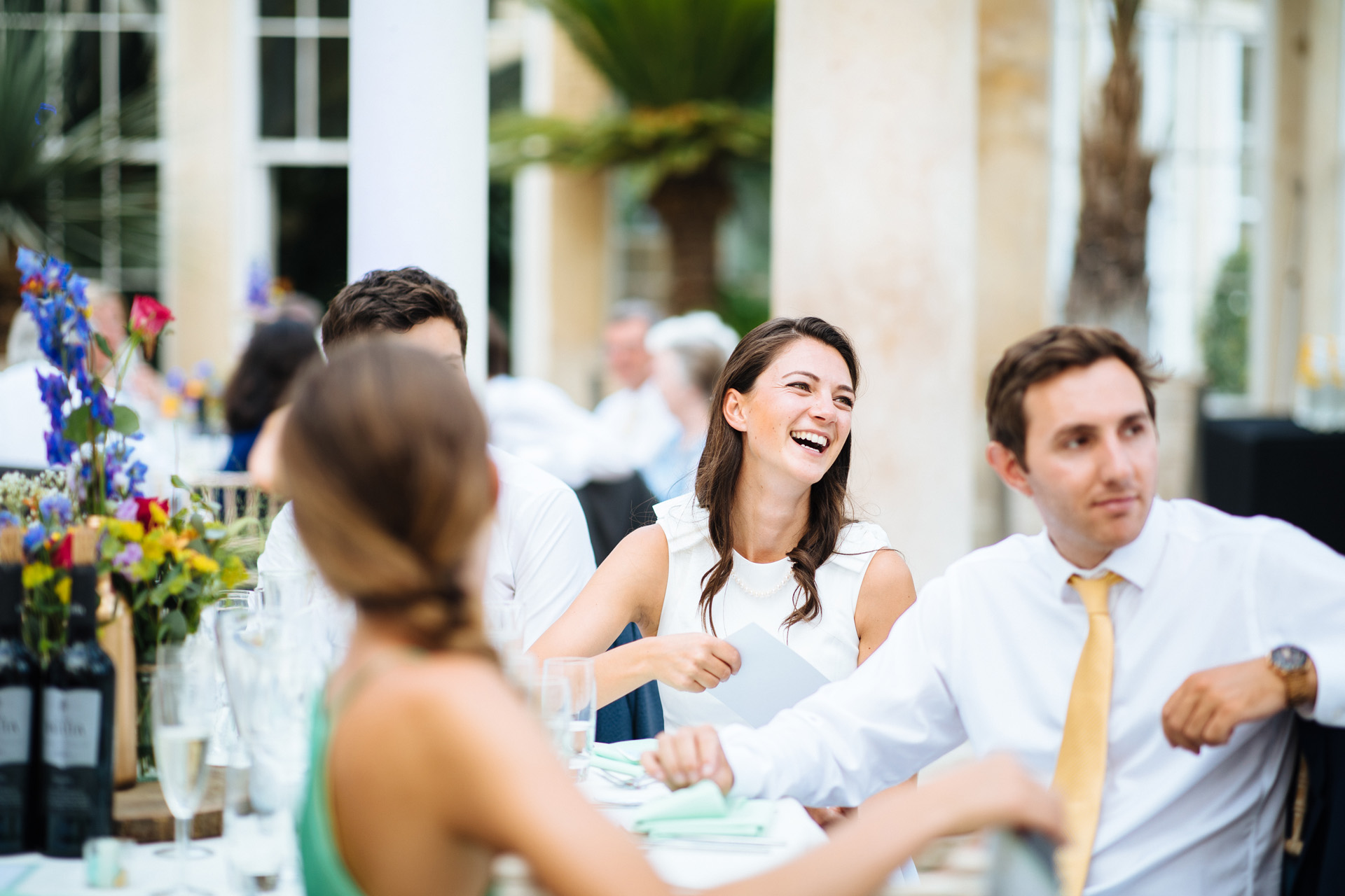 lady with brown hair laughing at grooms speech