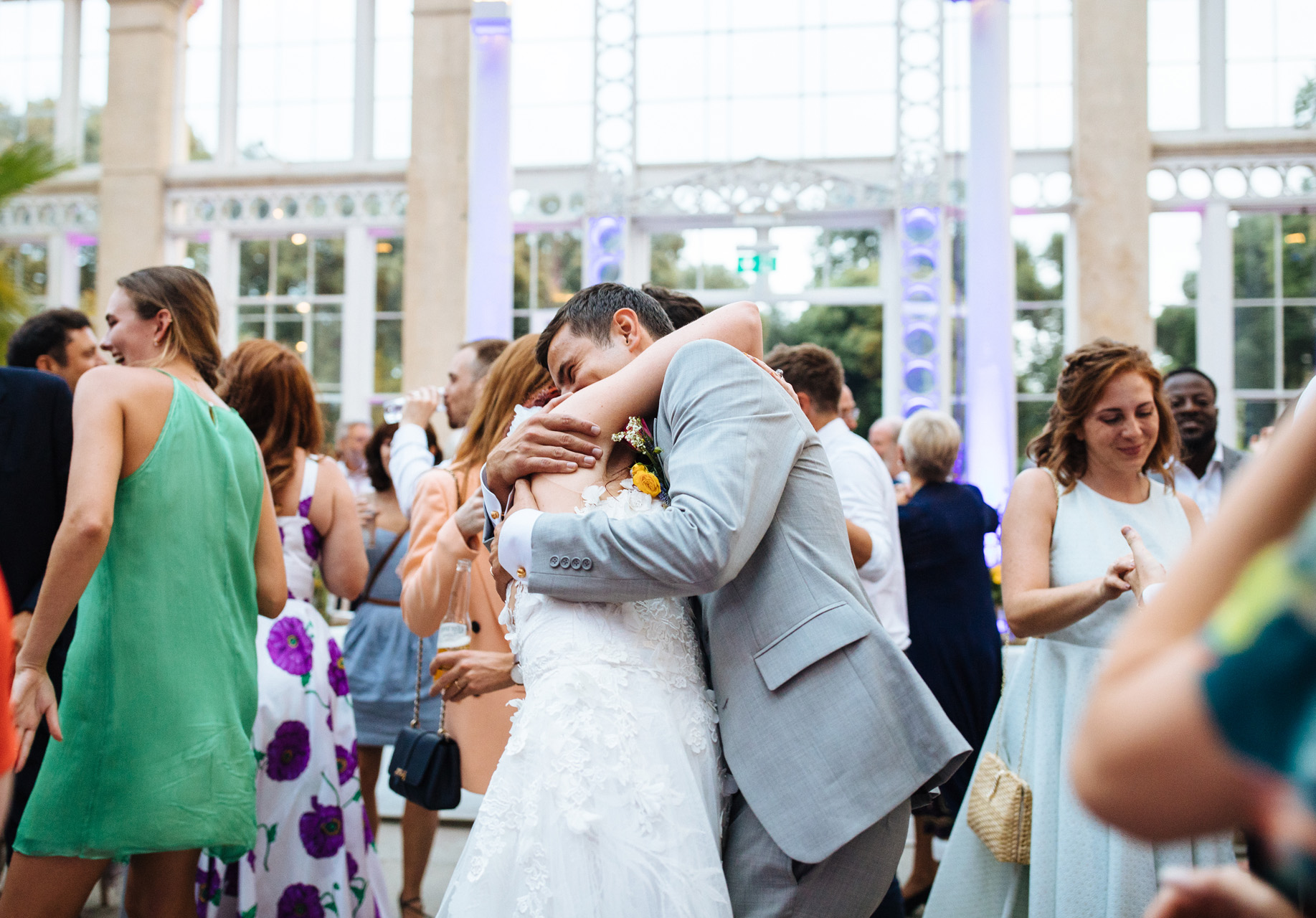 bride and groom hug each other tightly as their wedding guests join them in the first dance at syon park
