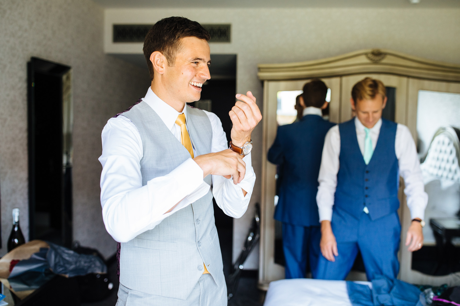 groom laughing and putting cufflinks on at syon park