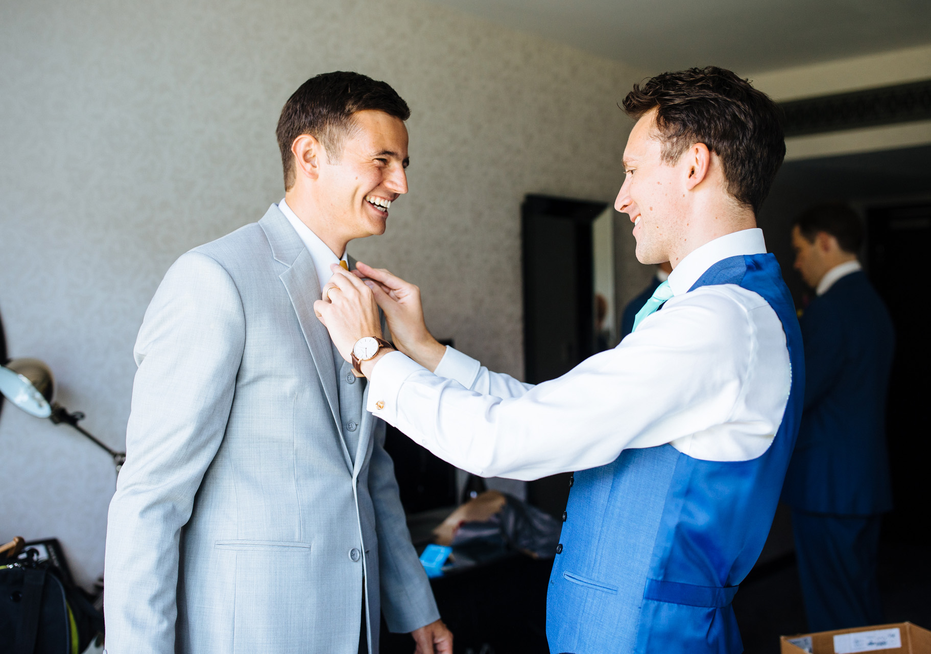 groom laughing at groomsman helping him with his tie