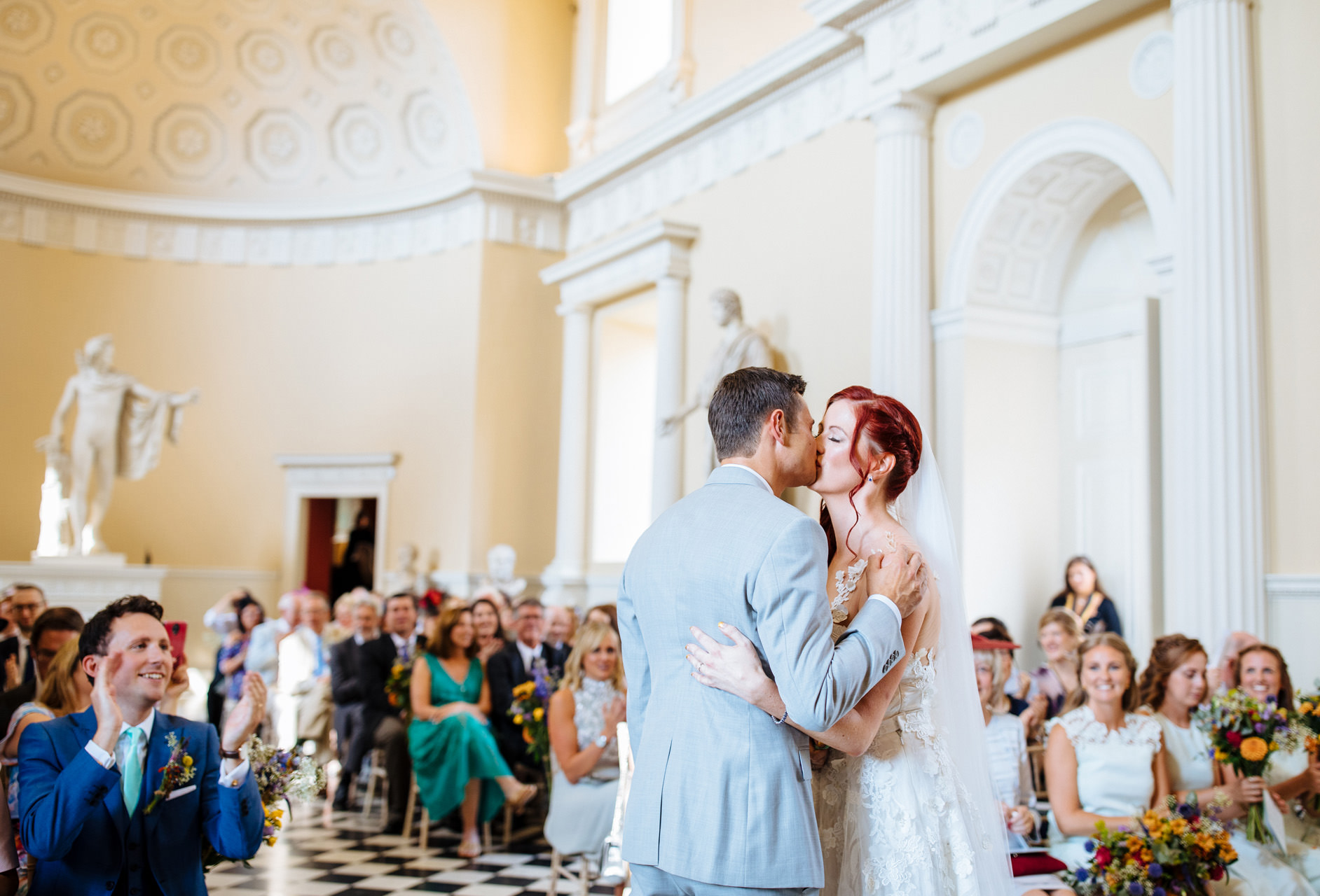 bride and groom share first kiss as husband and wife in grand room at syon park