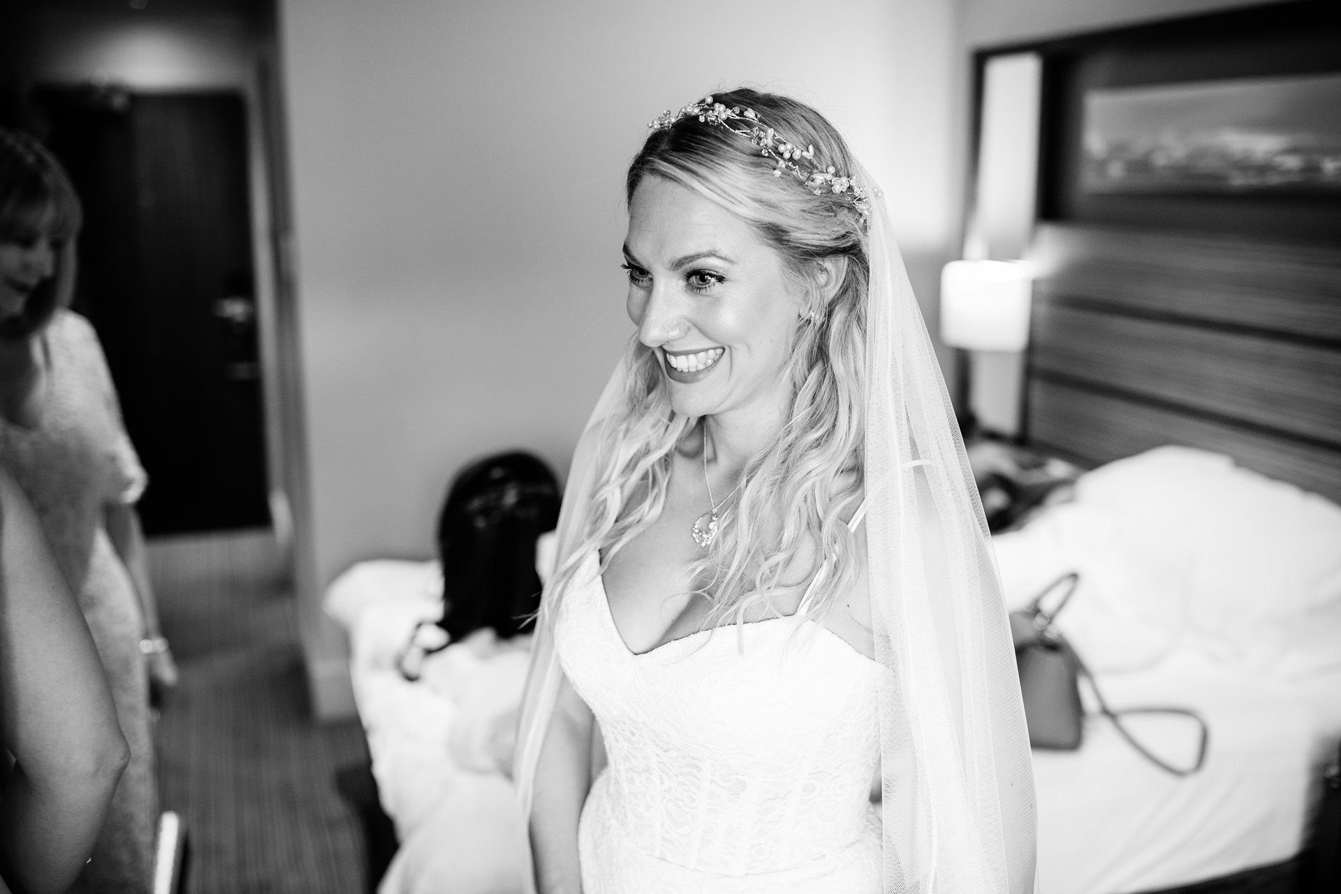 bride smiling excitedly as her dress is put on