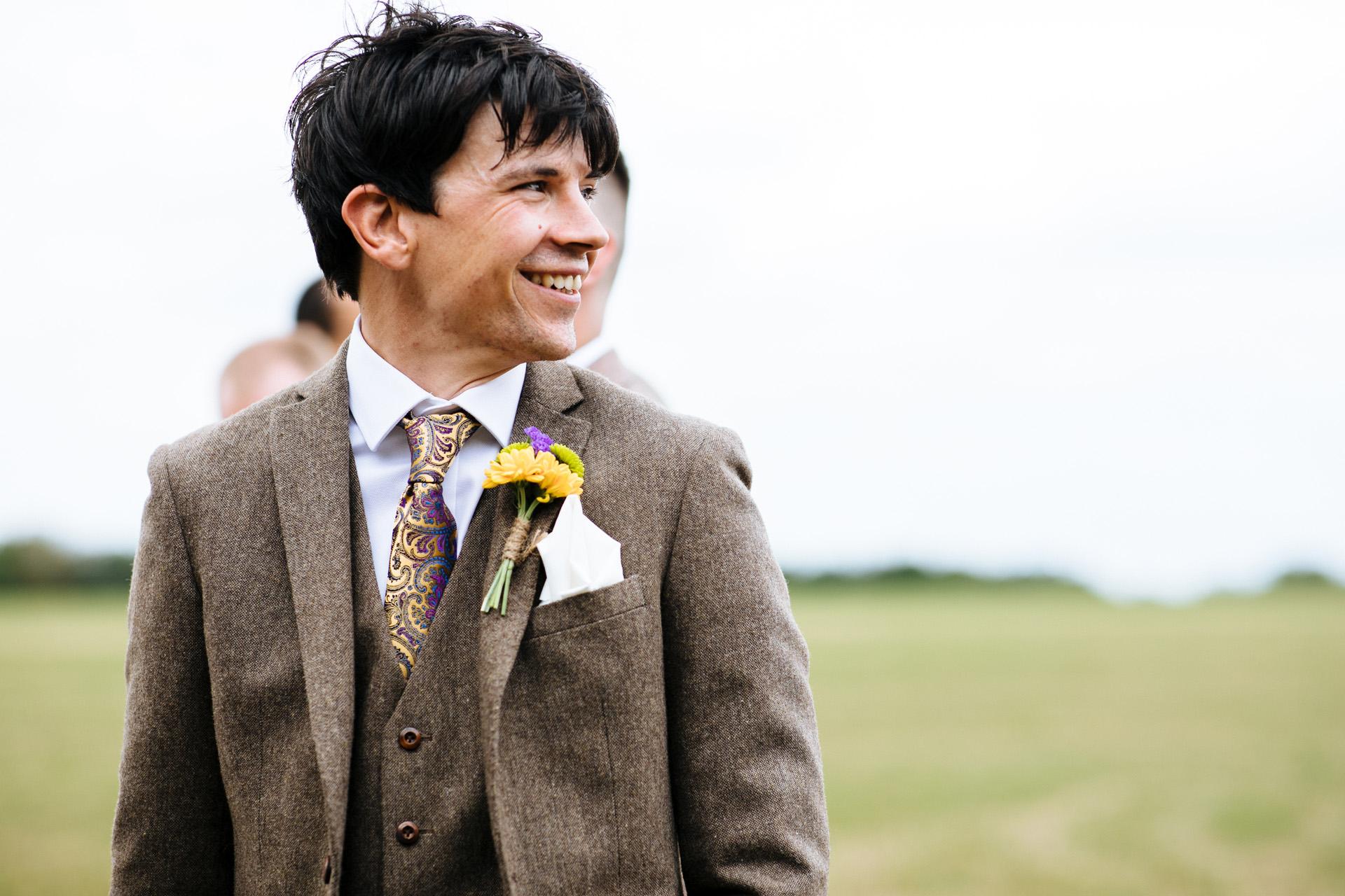 groom in brown tweed suit looking down the aisle smiling