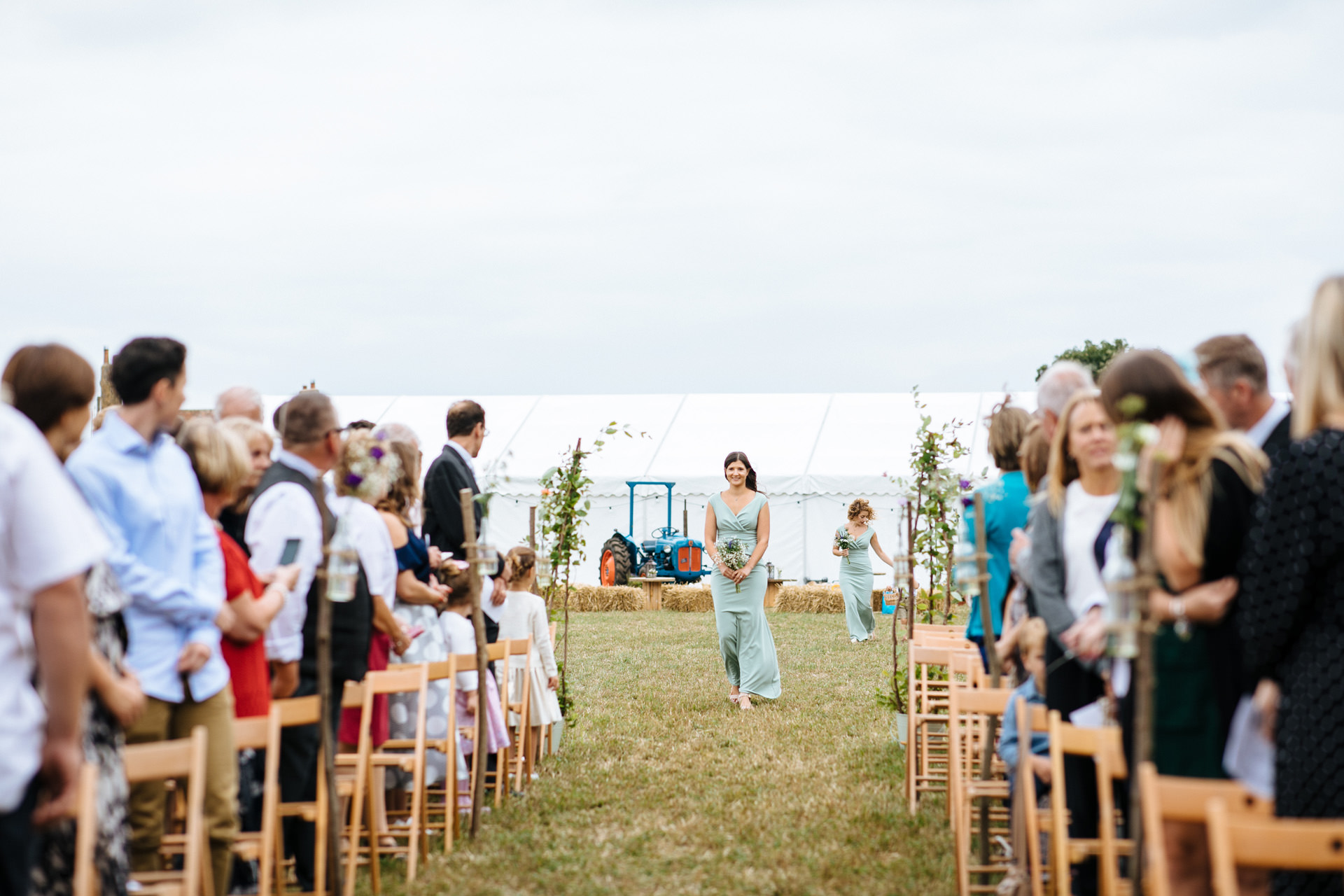 bridesmaid in green coming down the aisle at outdoor wedding ceremony in Kent