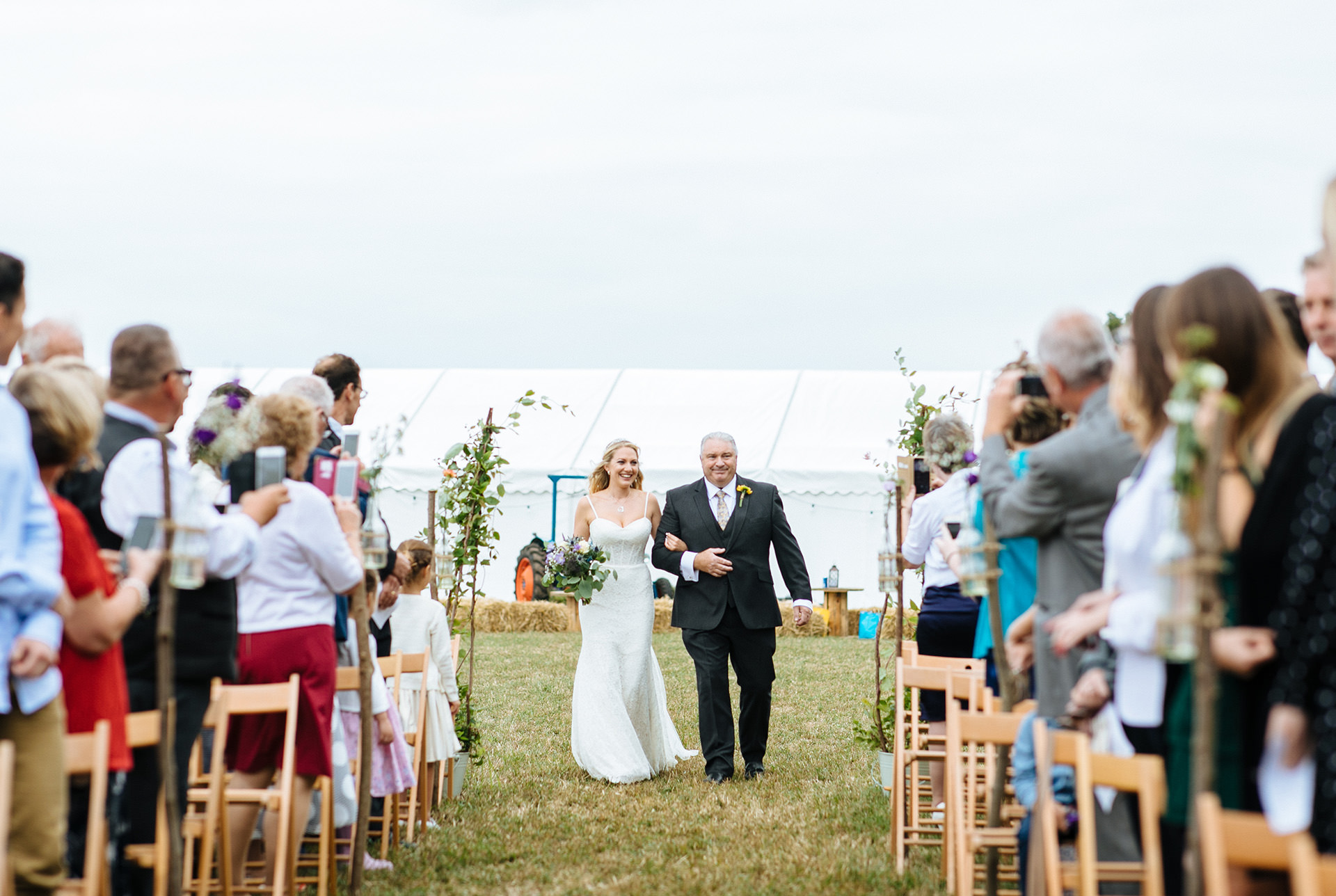 bride walking down the aisle with her dad at festival wedding in Kent