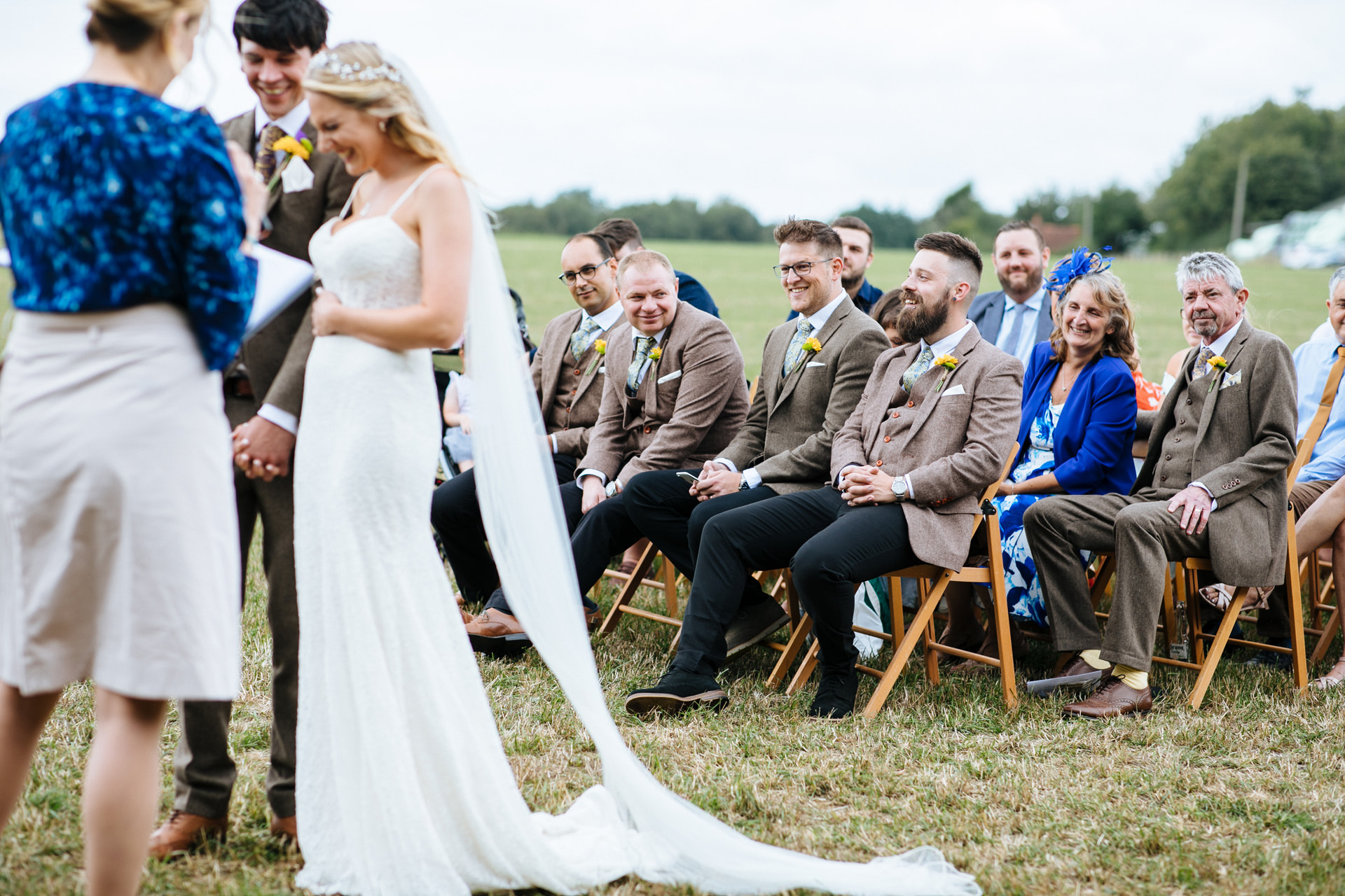 groomsmen in tweed watching the wedding ceremony and smiling