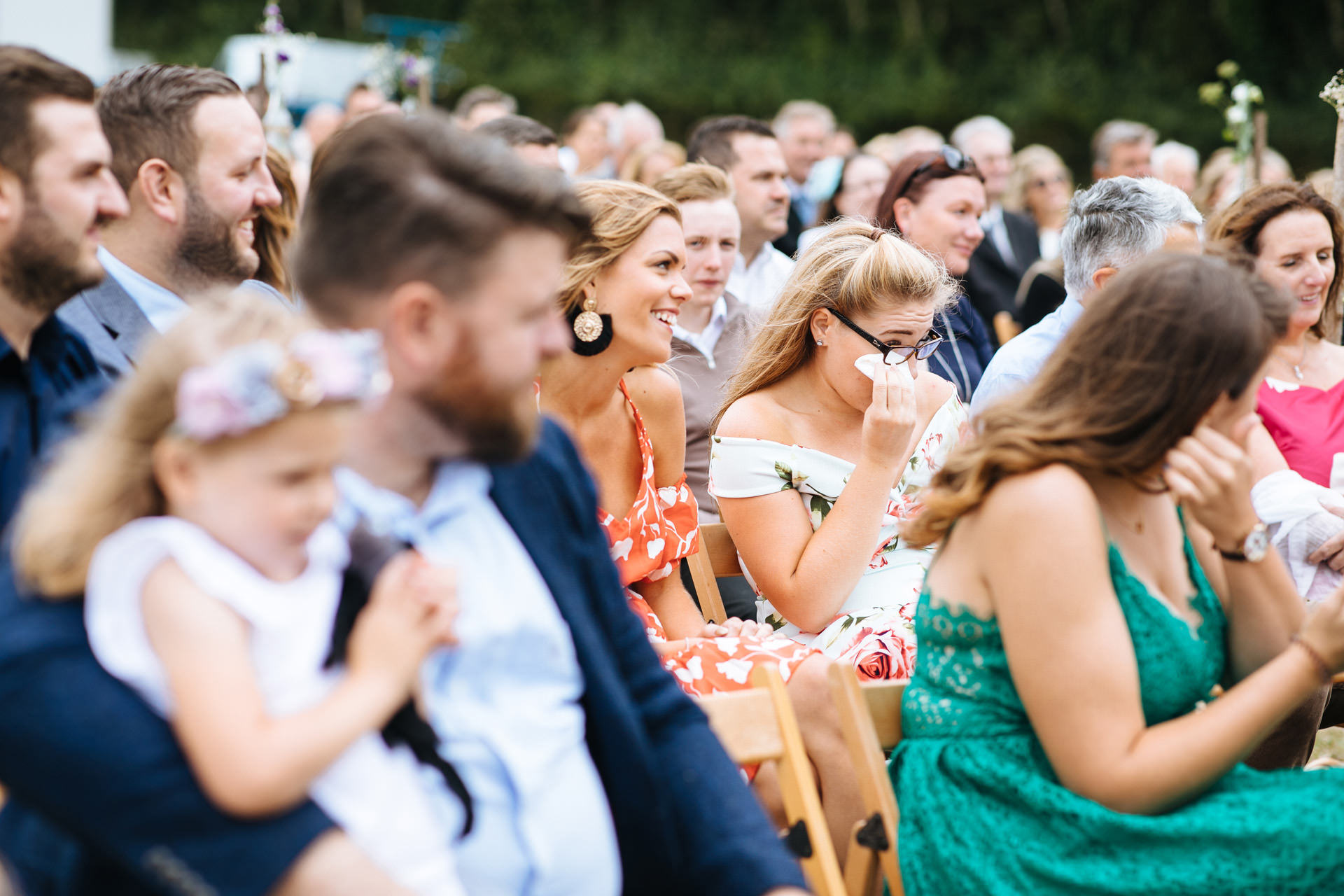 wedding guest dabbing her eyes with tissue during wedding ceremony