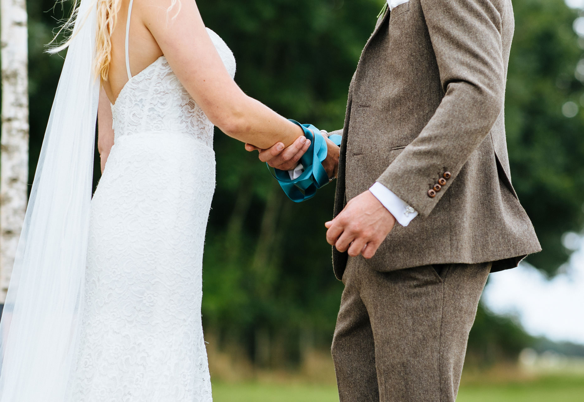 blue ribbon around couples hands at hand fasting wedding ceremony