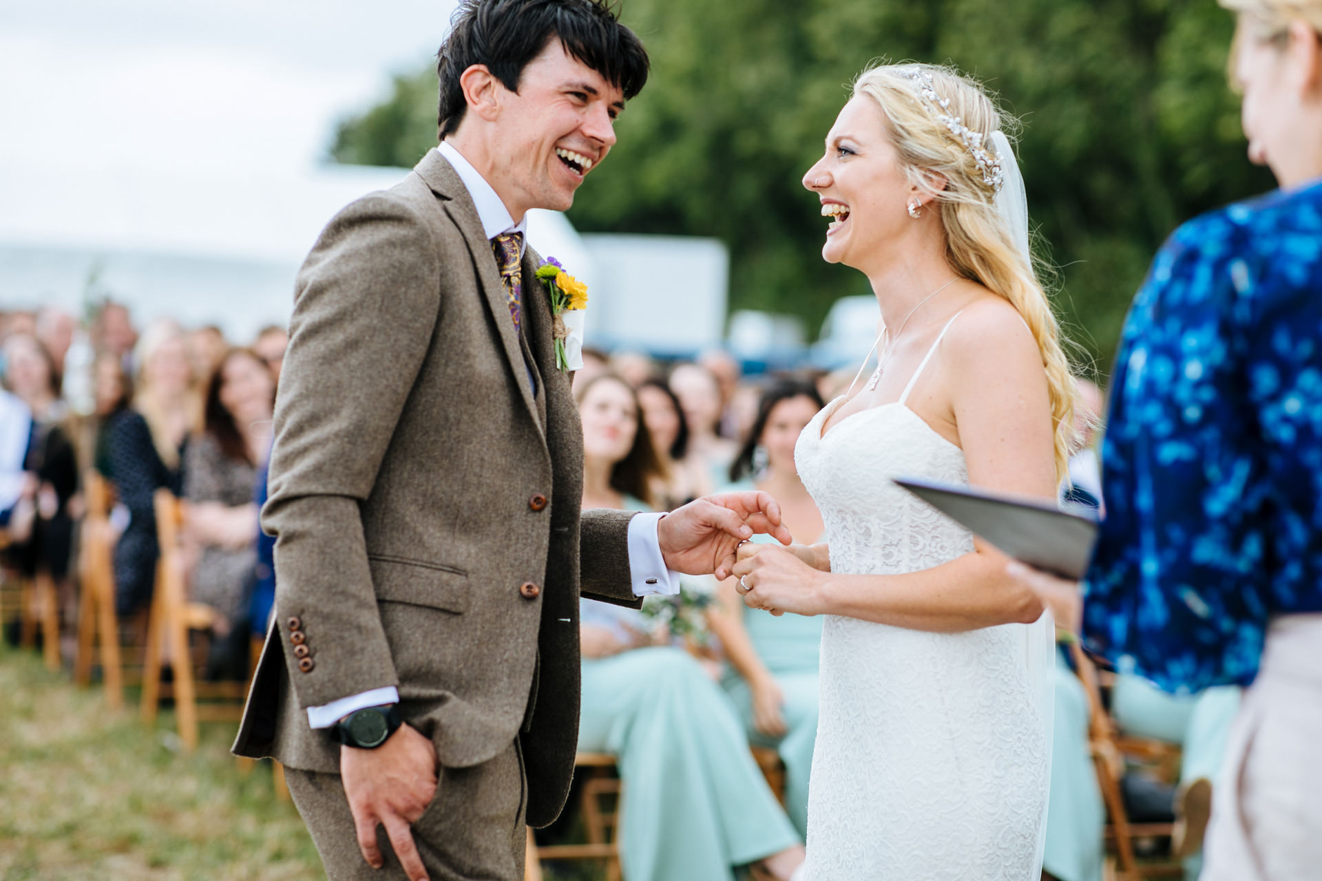 bride and groom laughing and exchanging rings at festival wedding in Kent