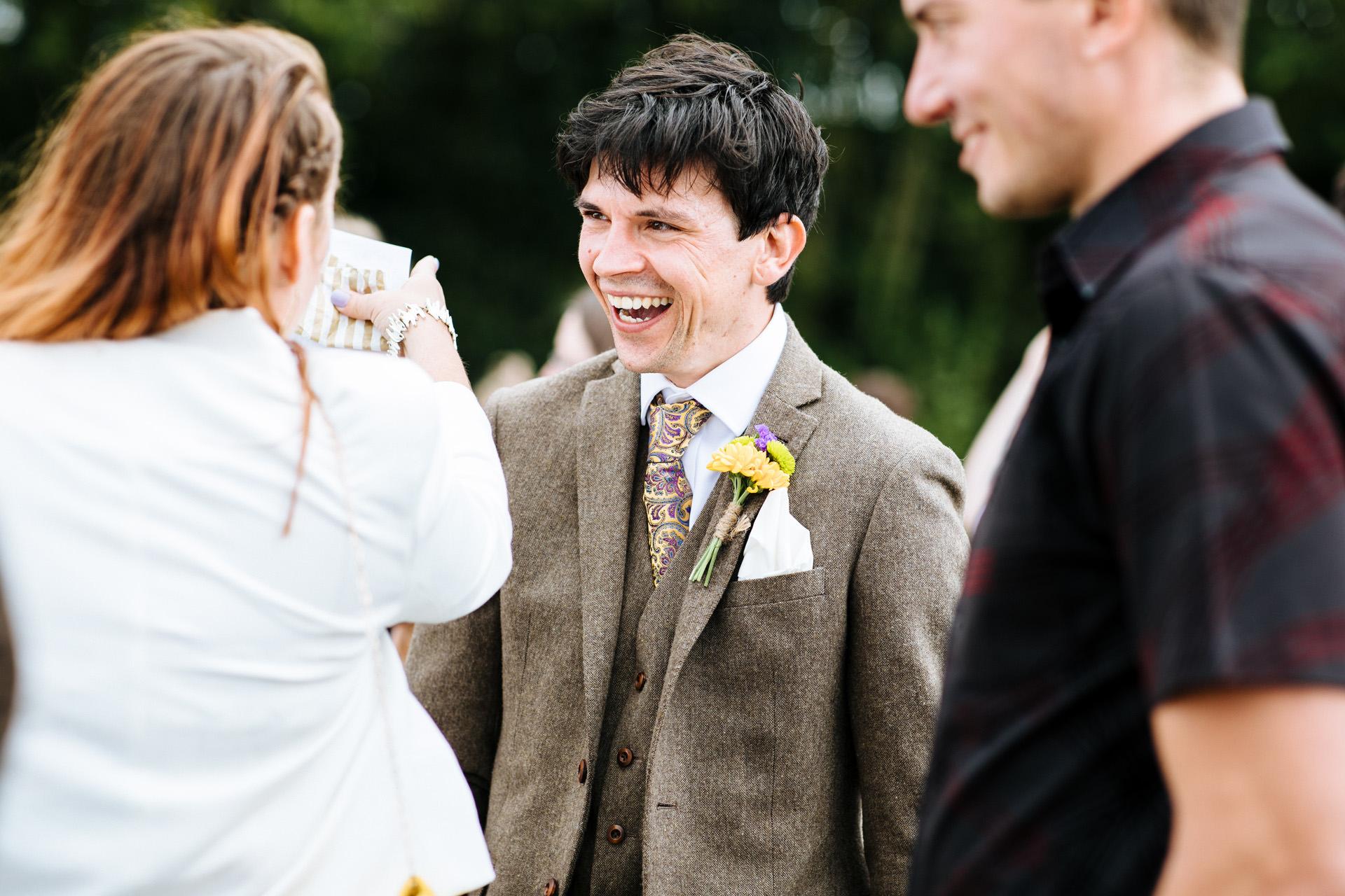 groom in tweed and dark hair laughing