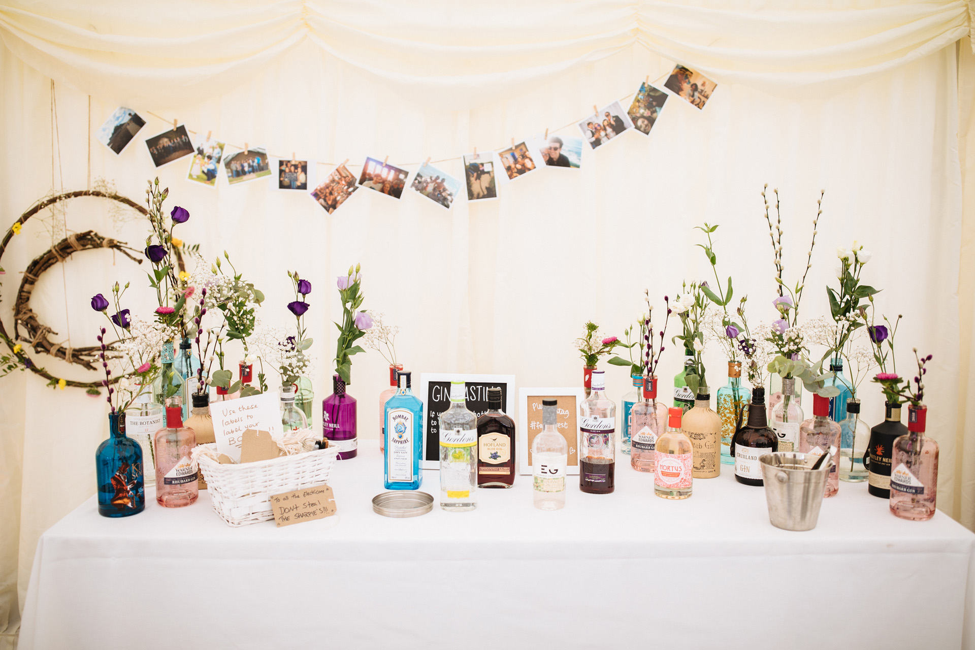 wedding decor assorted gin bottles and flowers