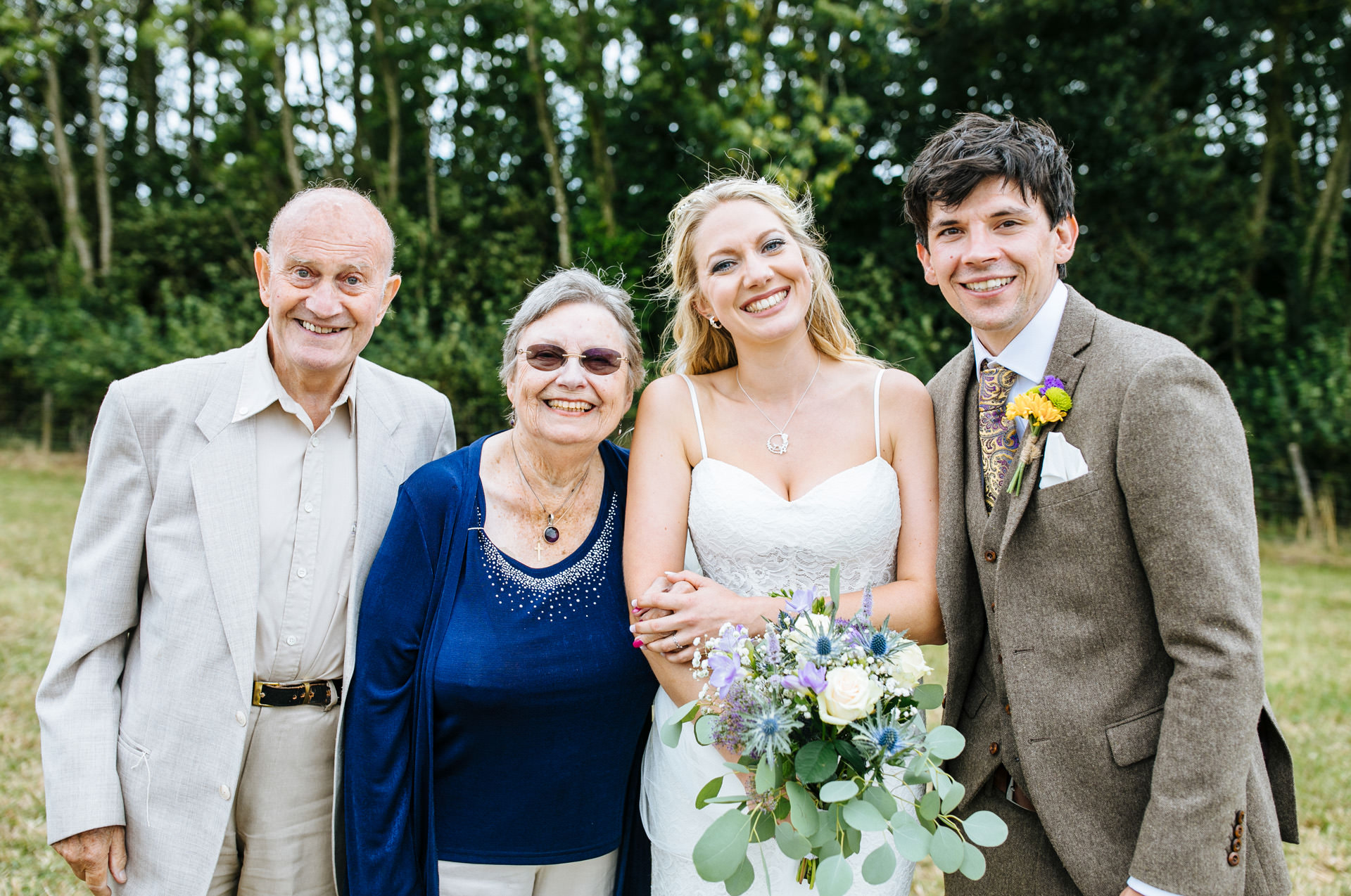 bride and groom posing with her grandparents