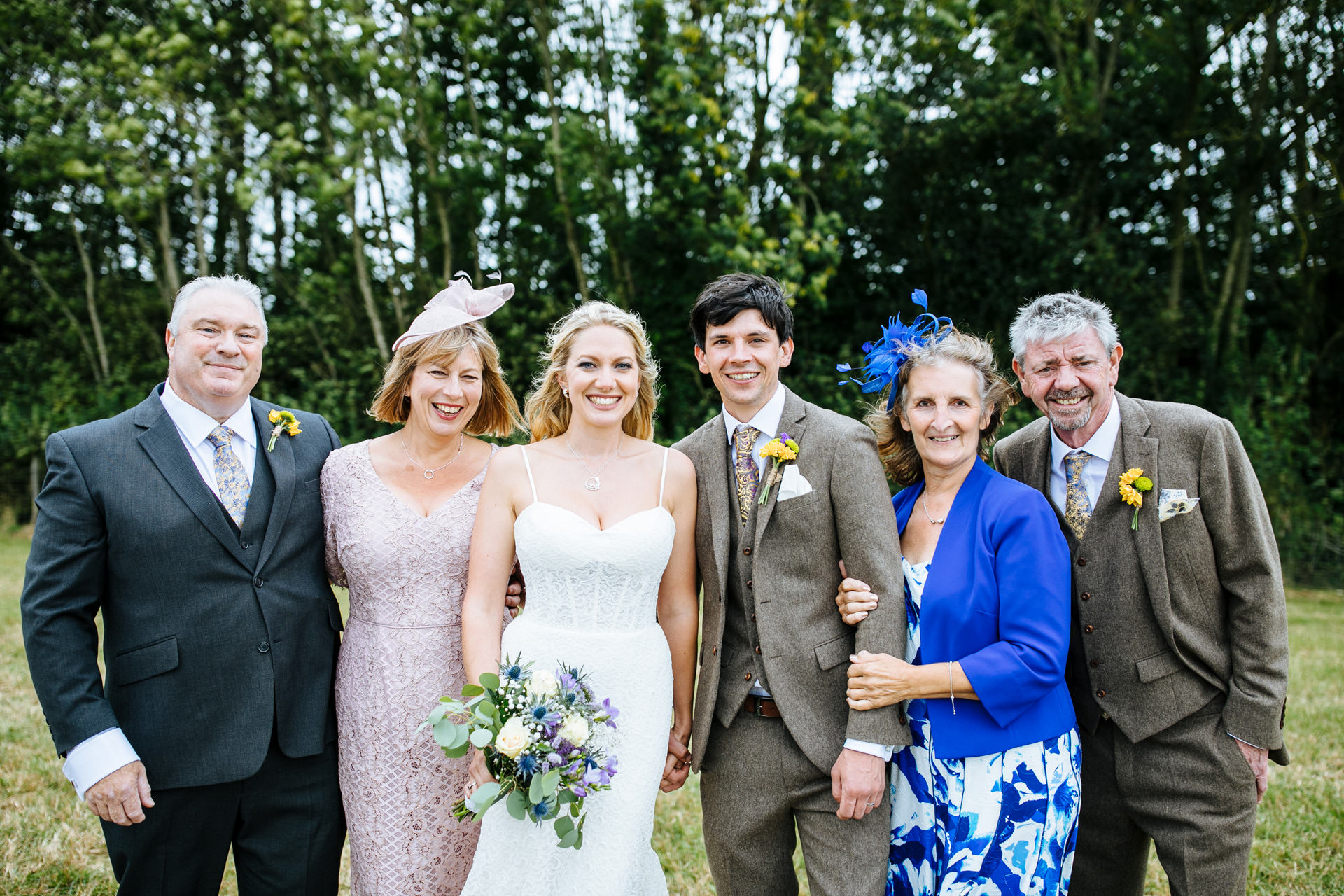 bride and groom posing with their parents at festival wedding in Kent