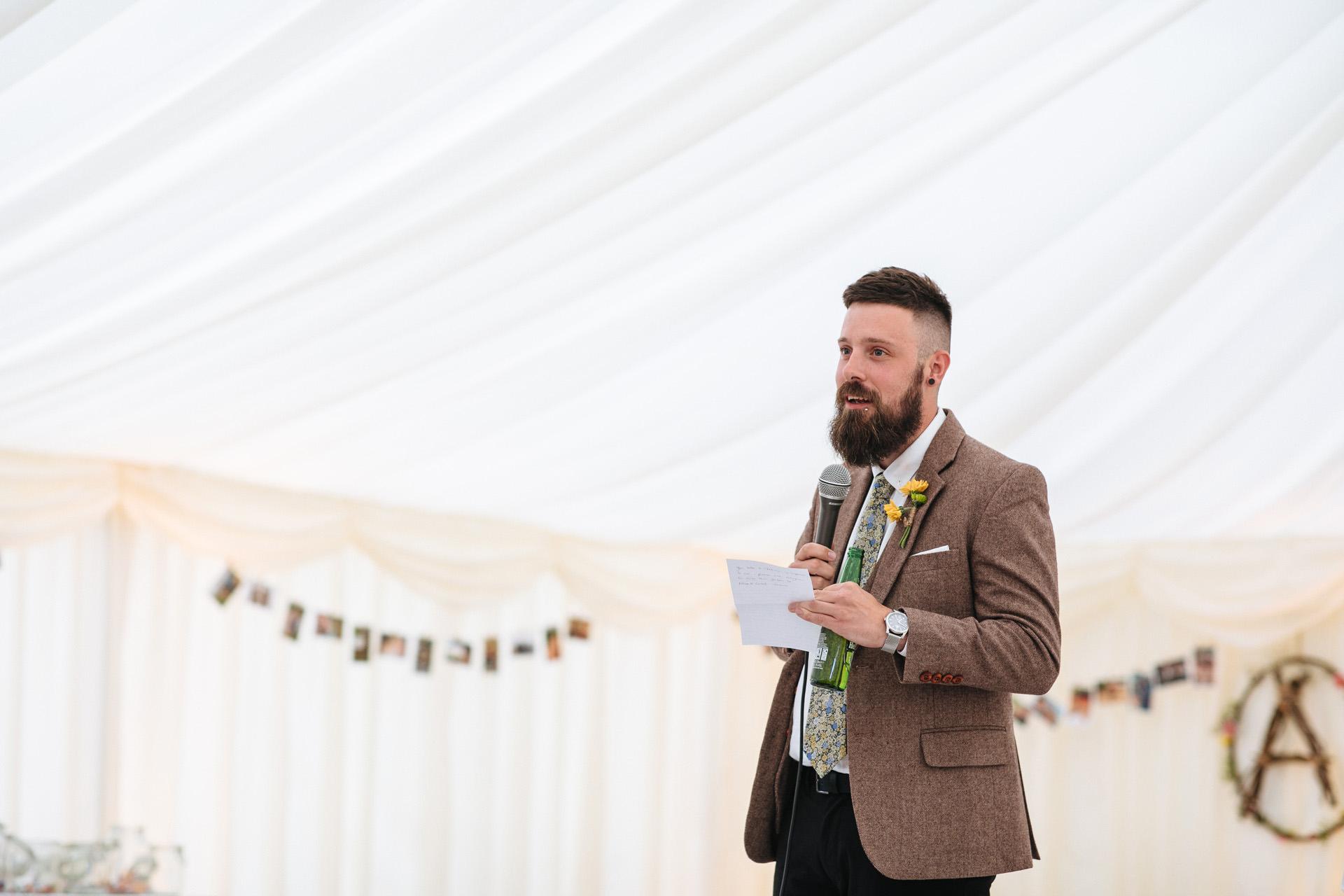best man in tweed suit in marquee giving best man speech