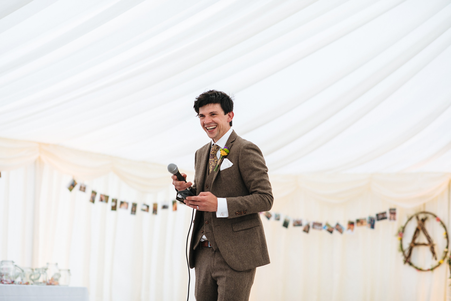 groom in tweed suit laughing and giving speech