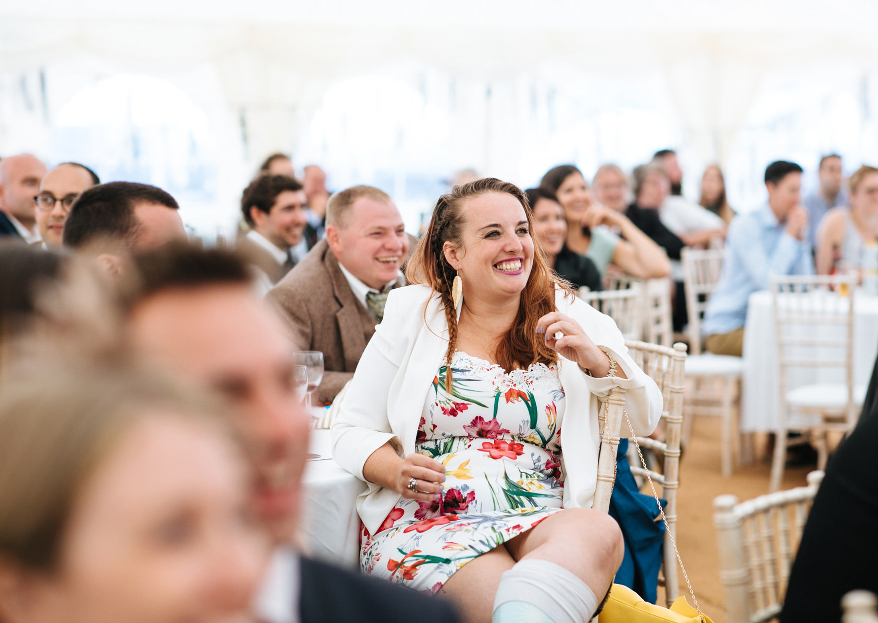 wedding guest smiling at speeches in marquee at festival wedding