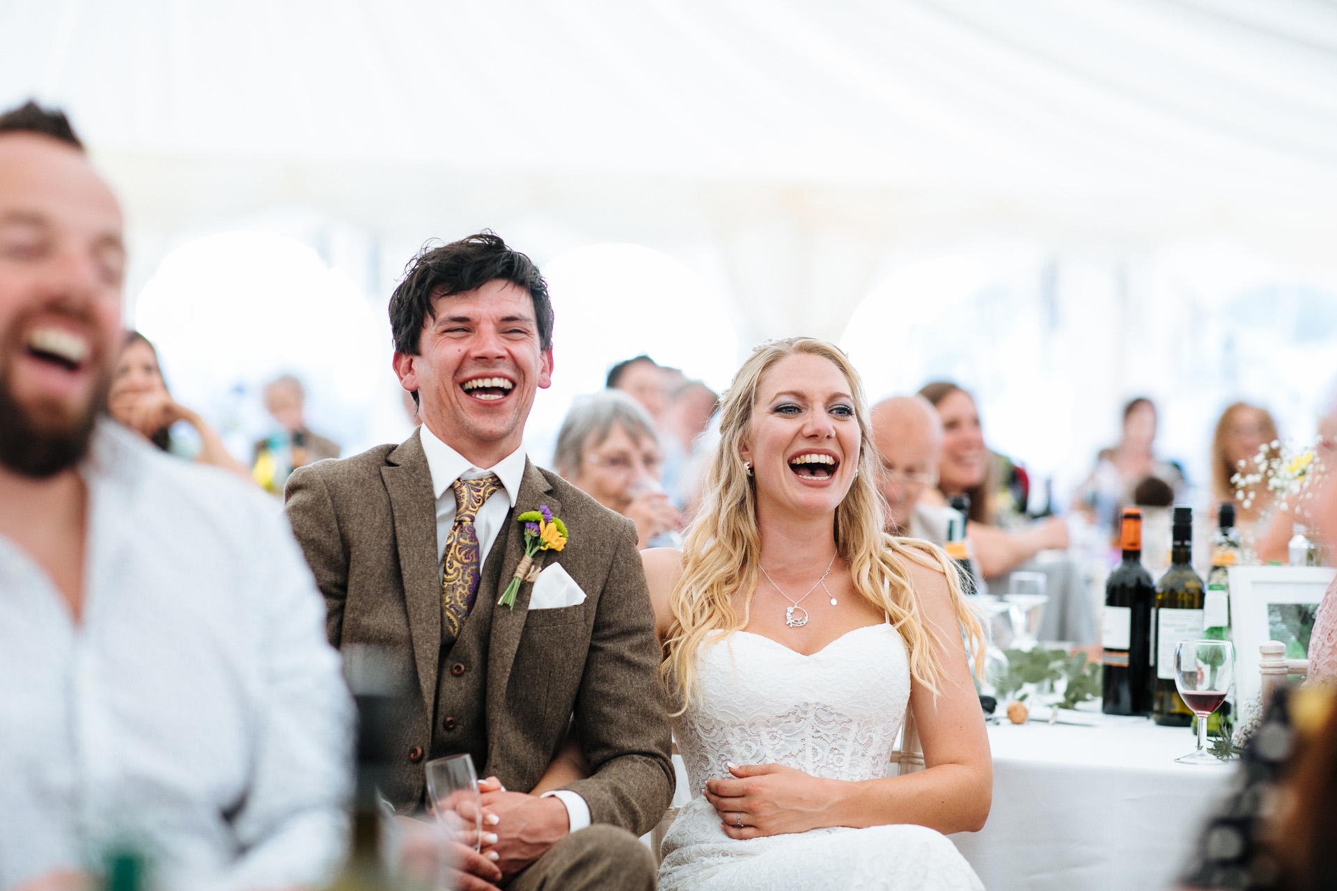 bride and groom laughing at best man wedding speech in marquee