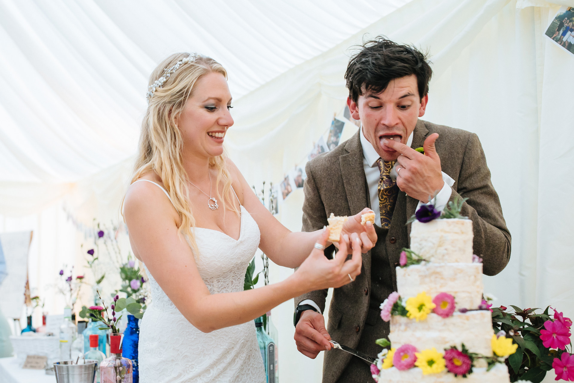 bride and groom cutting the cake at festival wedding in Kent