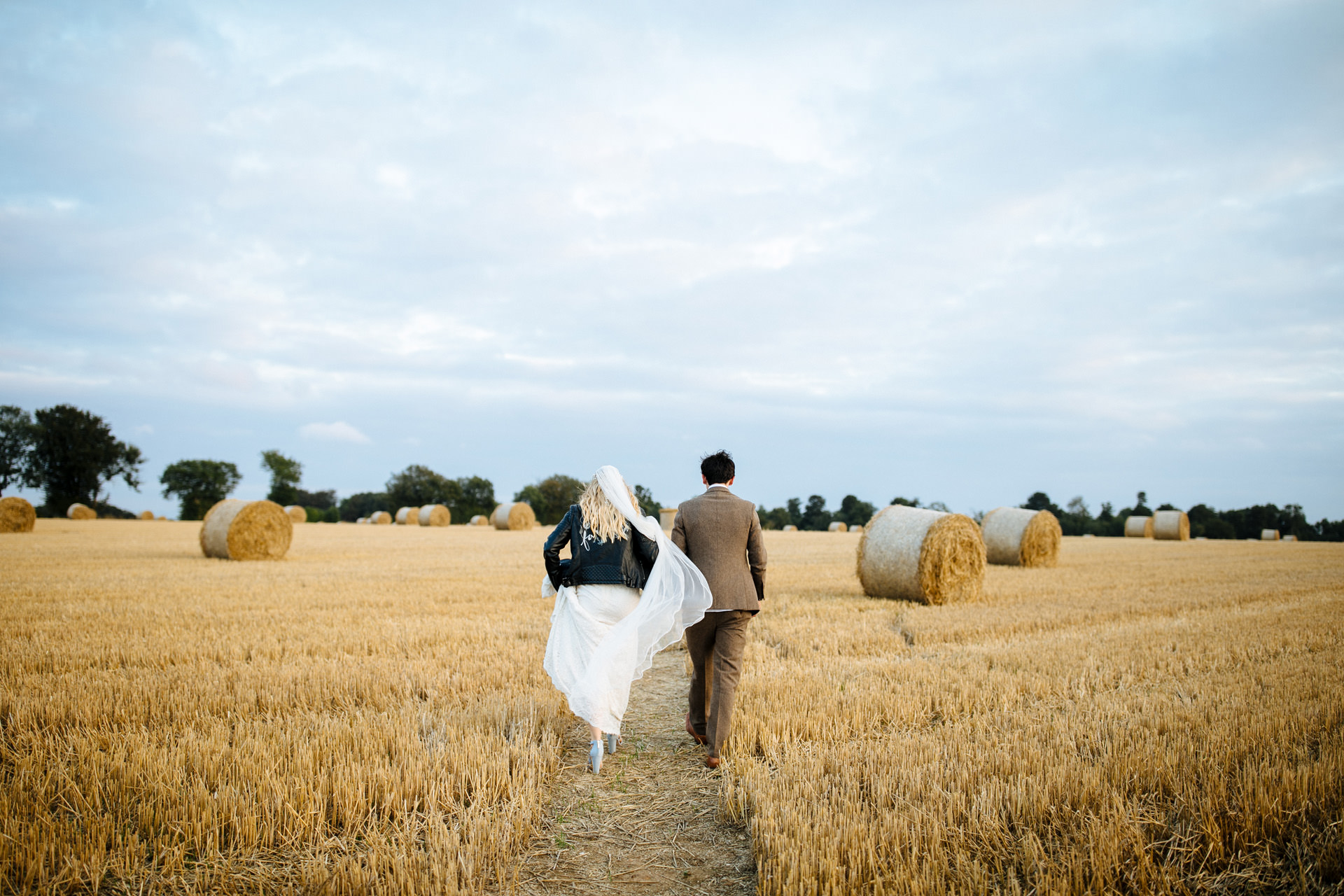bride and groom walking in corn field at sunset at festival wedding
