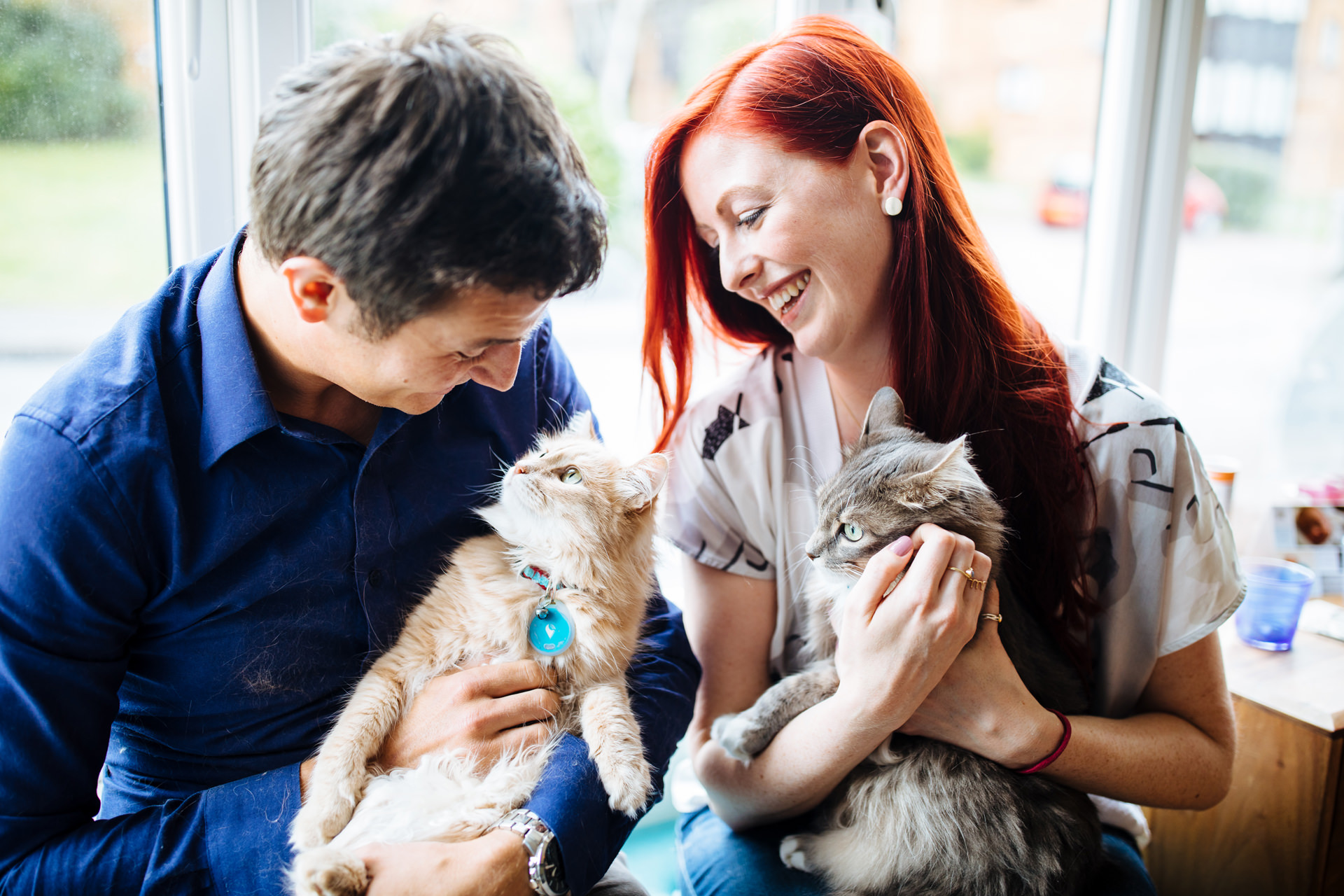 couple laughing and cuddling their cats