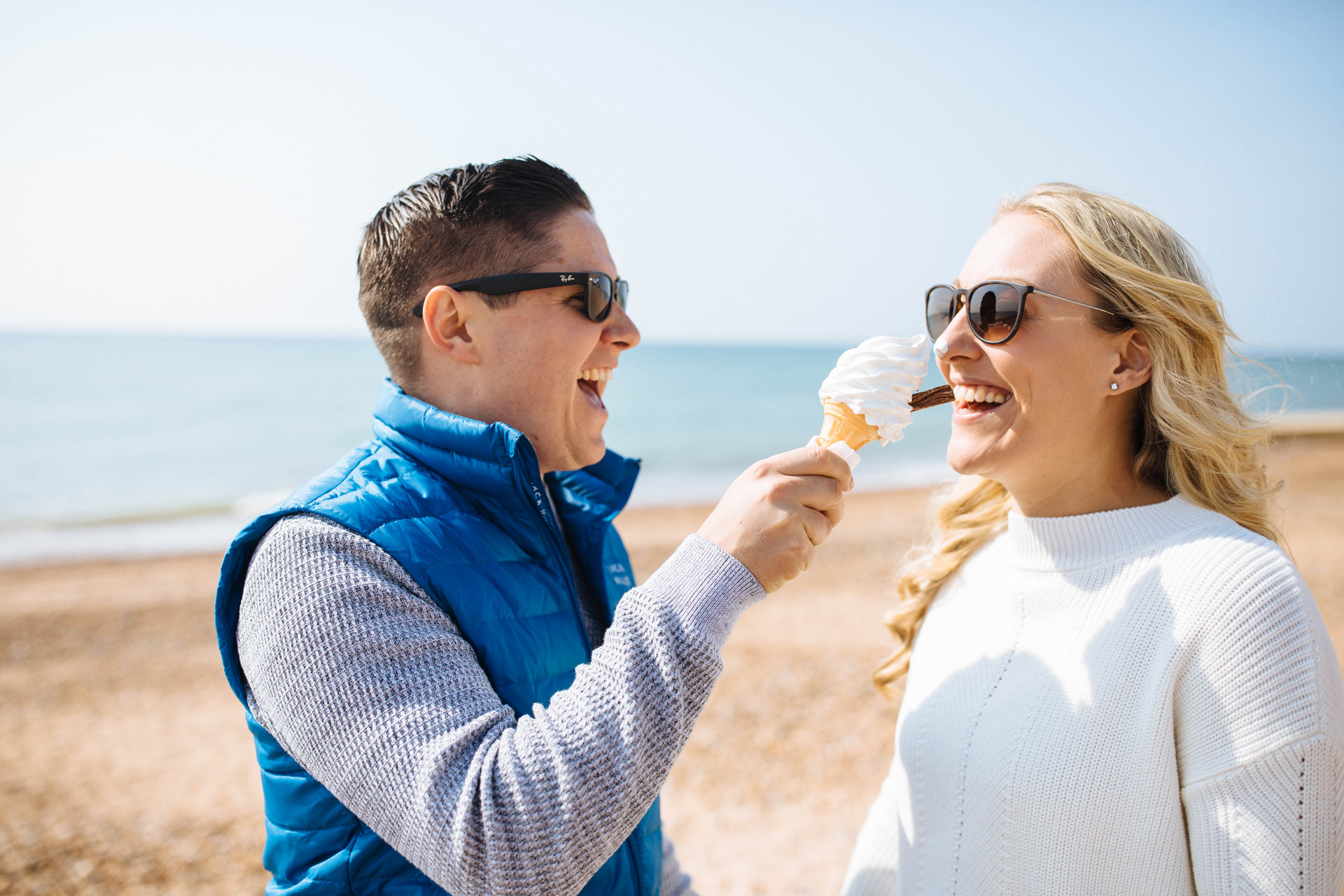 couple on the beach laughing with ice cream