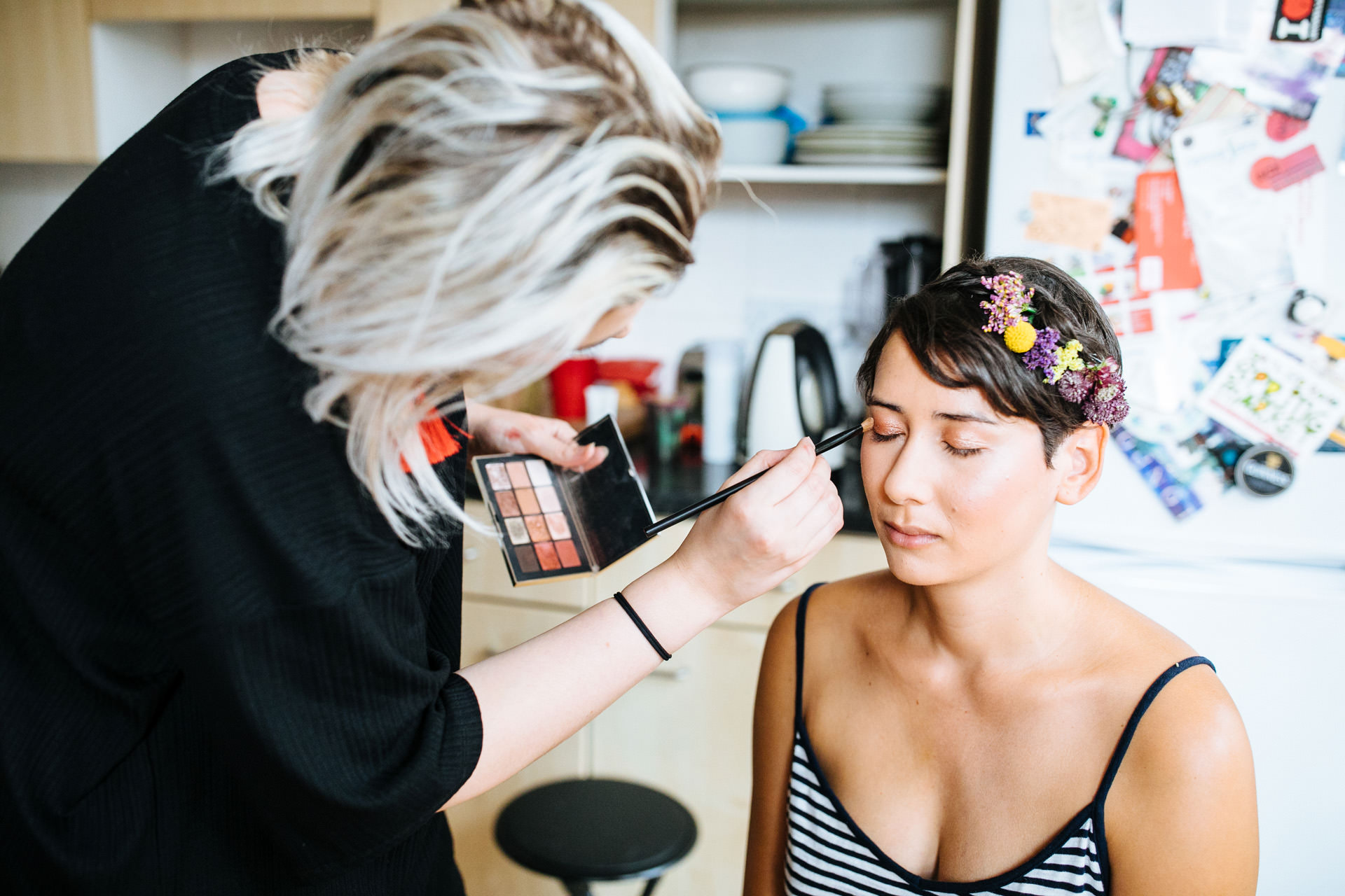 bride with flower crown and dark hair having make up done