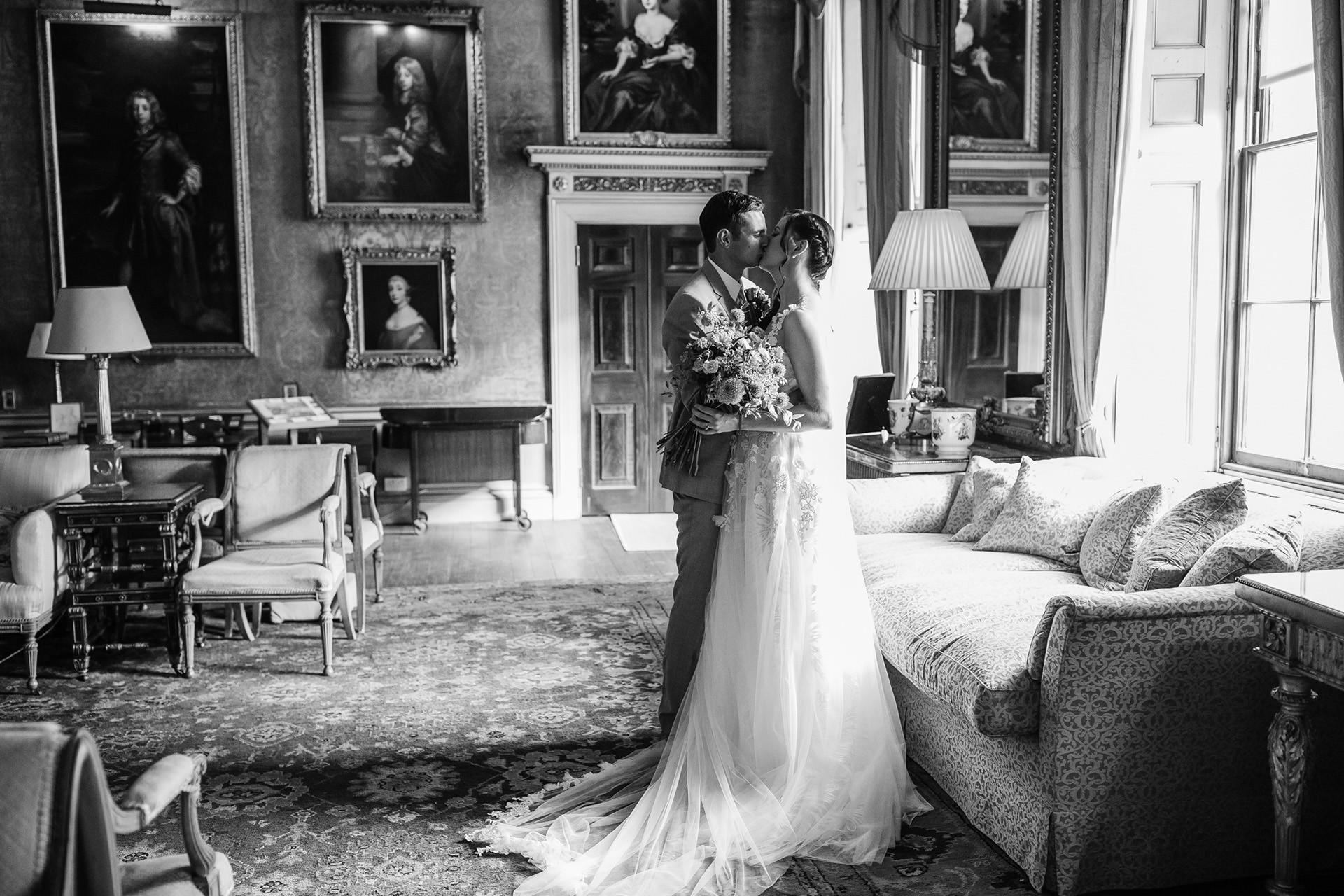bride and groom kissing in painting gallery room
