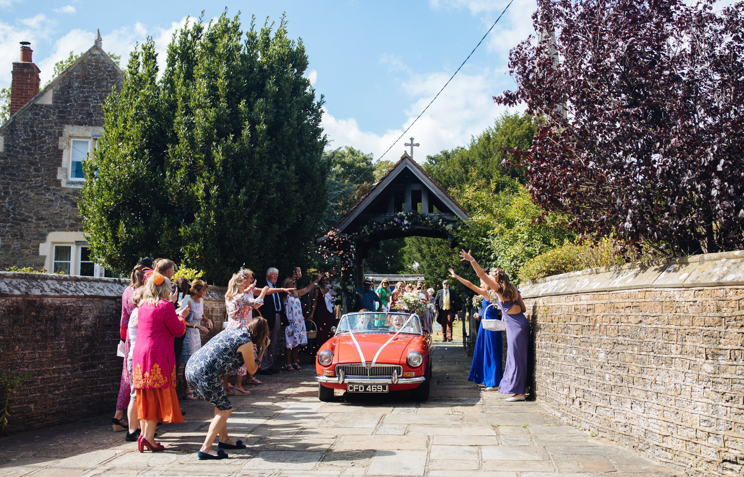 bride and groom leaving church in traditional red car