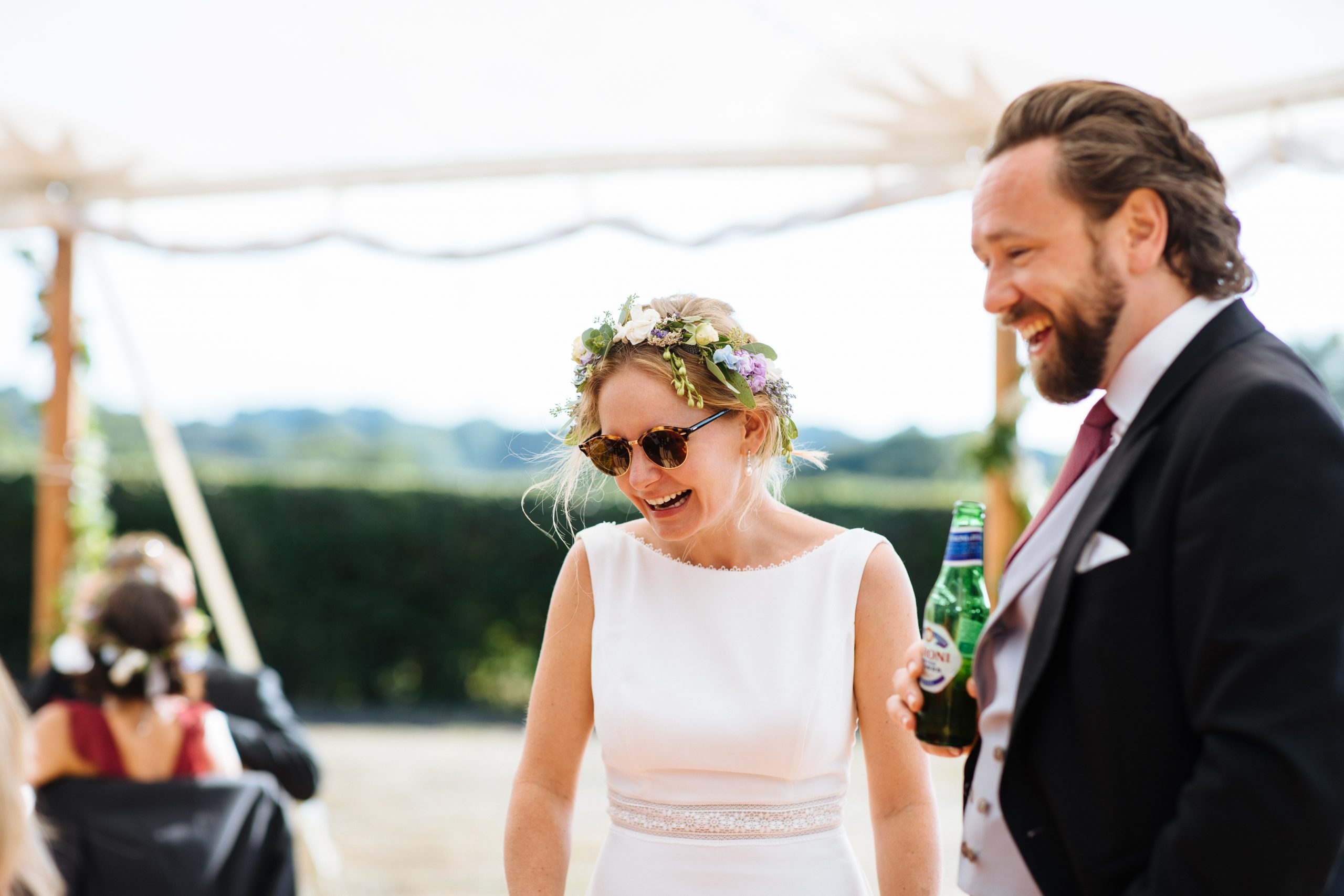 bride with flower crown and sunglasses laughing at Kent wedding