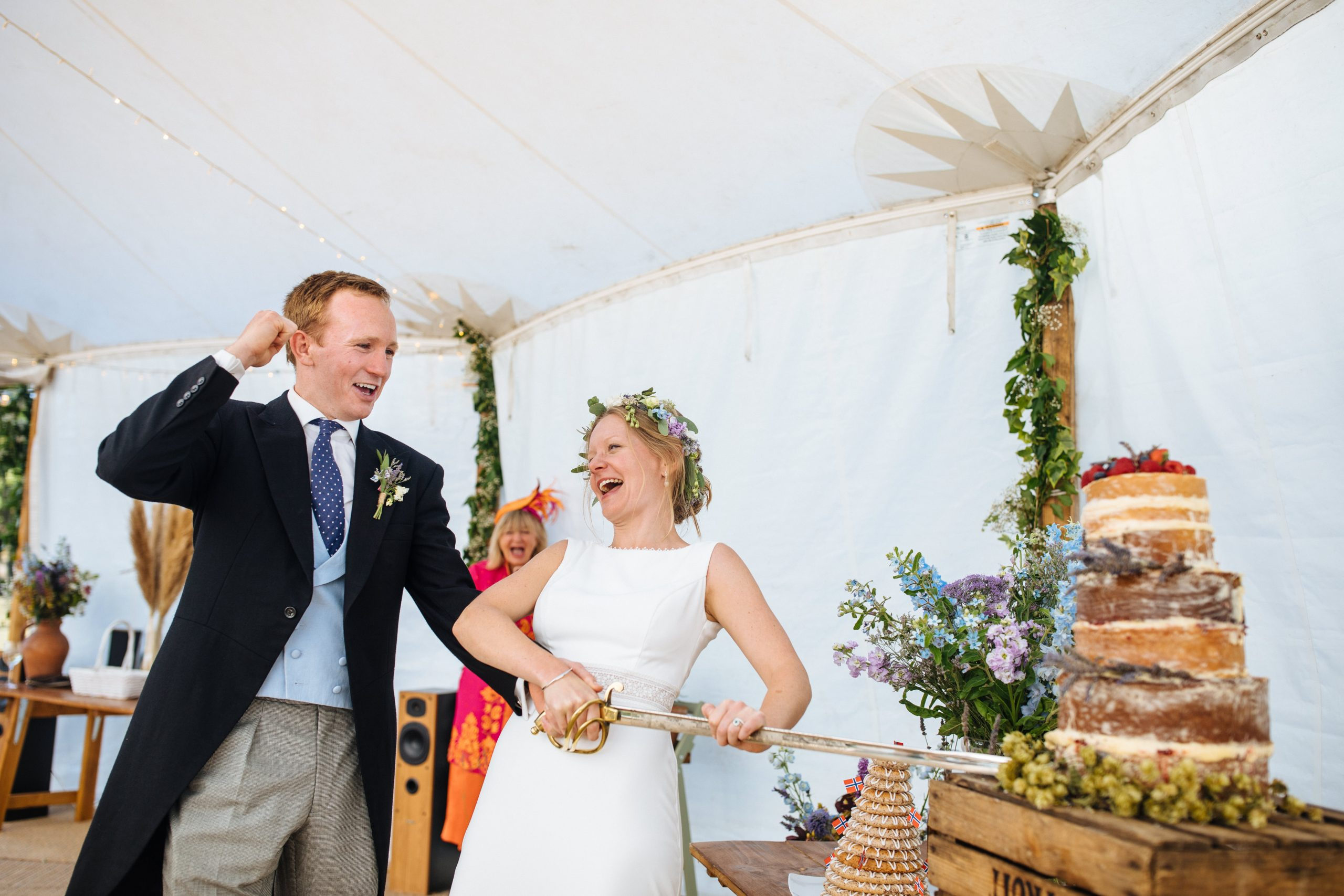 bride and groom cutting naked cake with sword and laughing