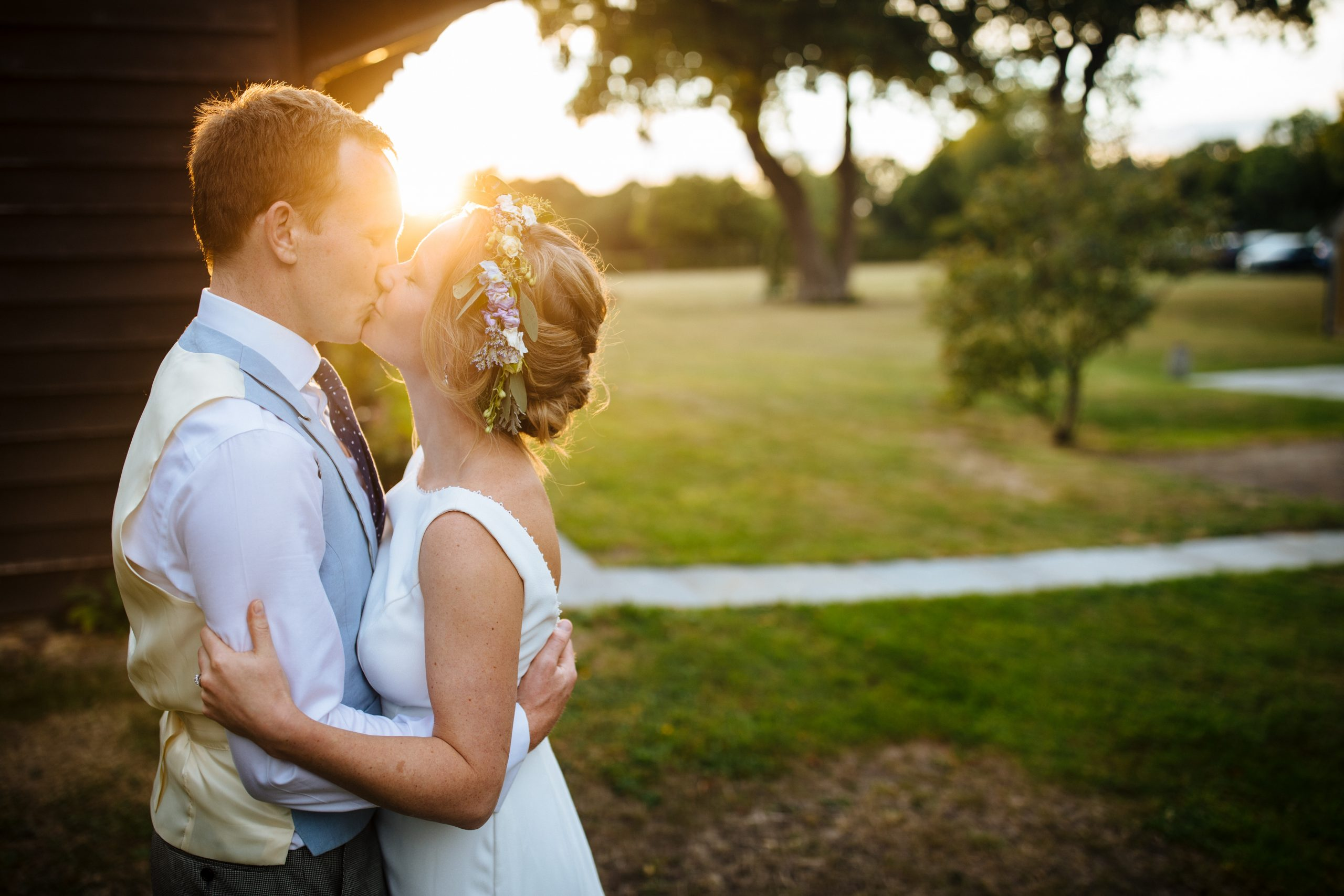 bride with flower crown kissing groom at sunset at Kent wedding