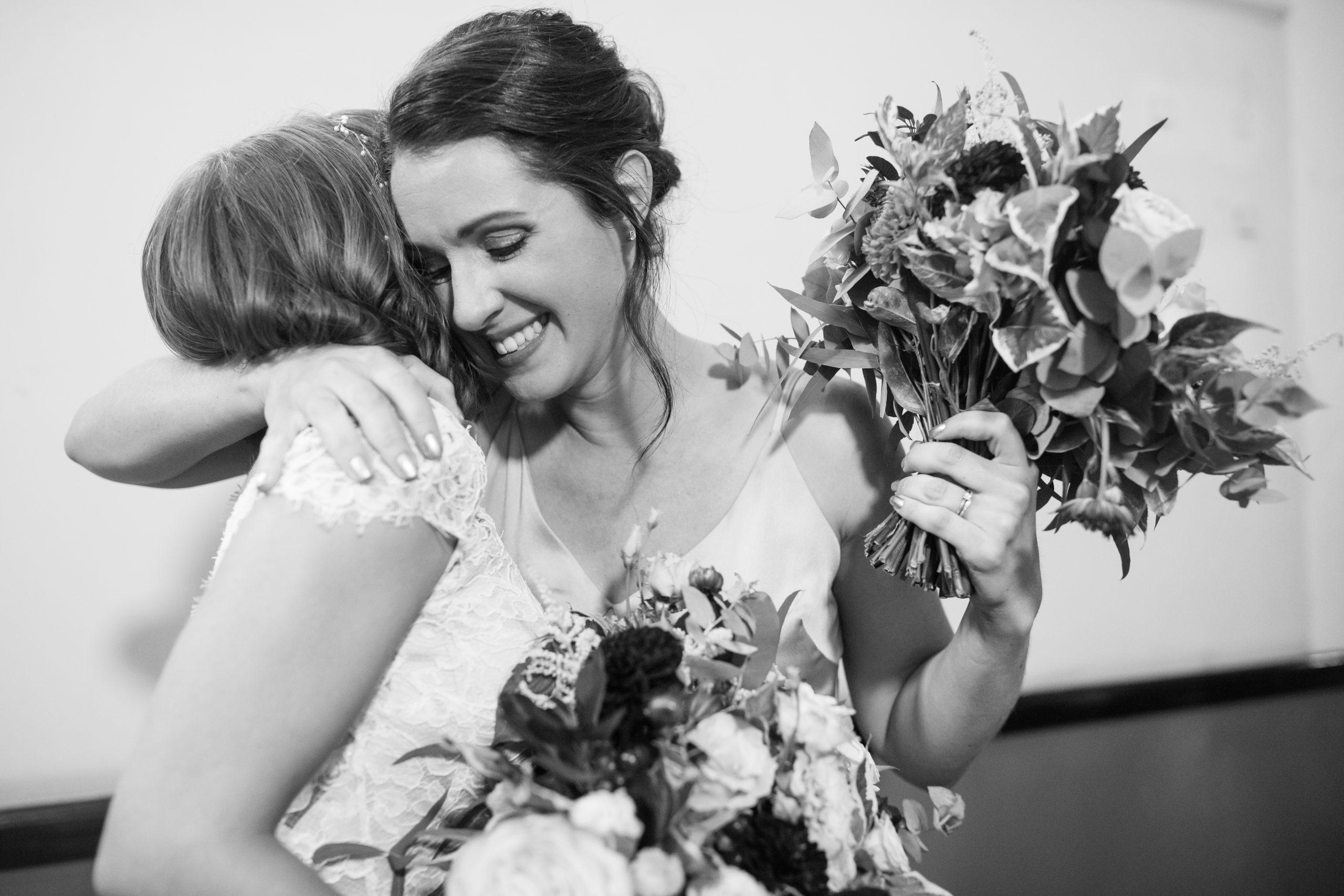 bridesmaid hugging bride at le gothique wedding