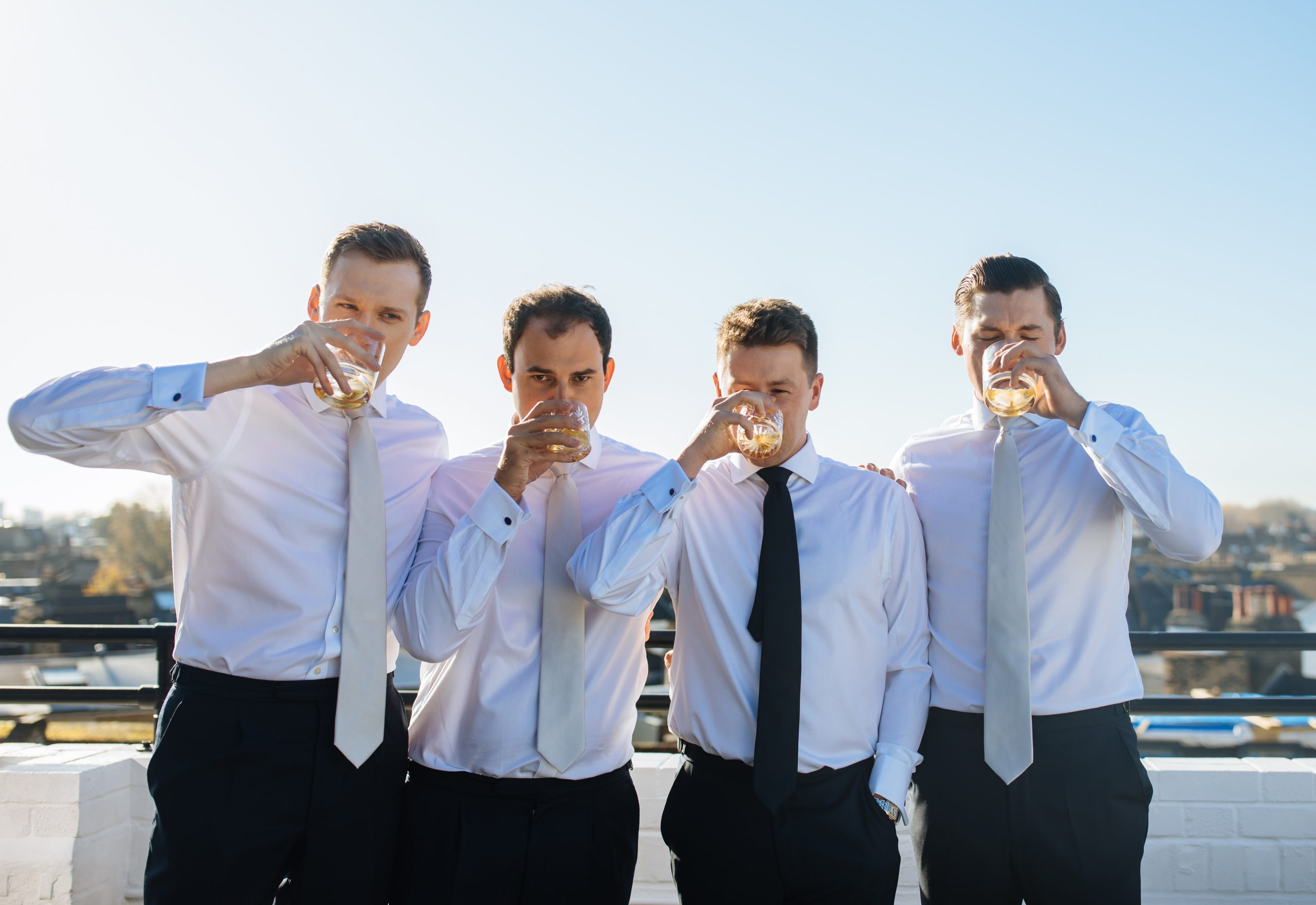 groomsmen drinking whisky on wedding morning