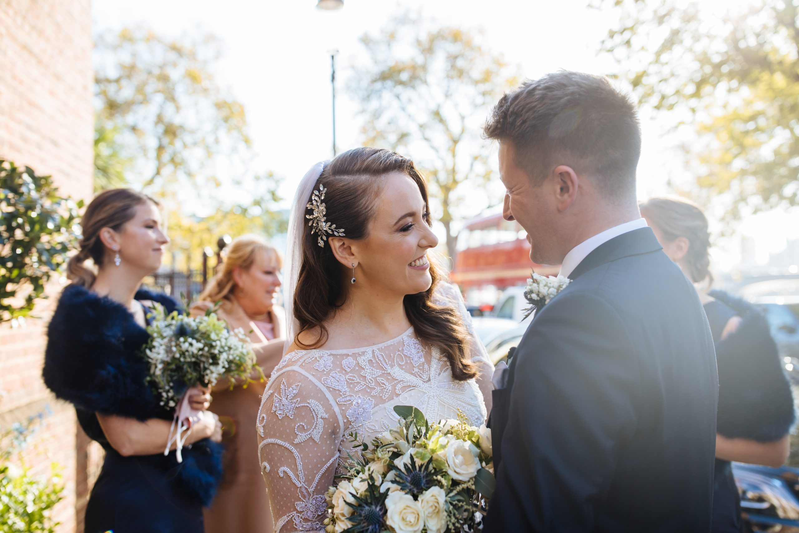 bride smiling at groom outside Chelsea old church wedding