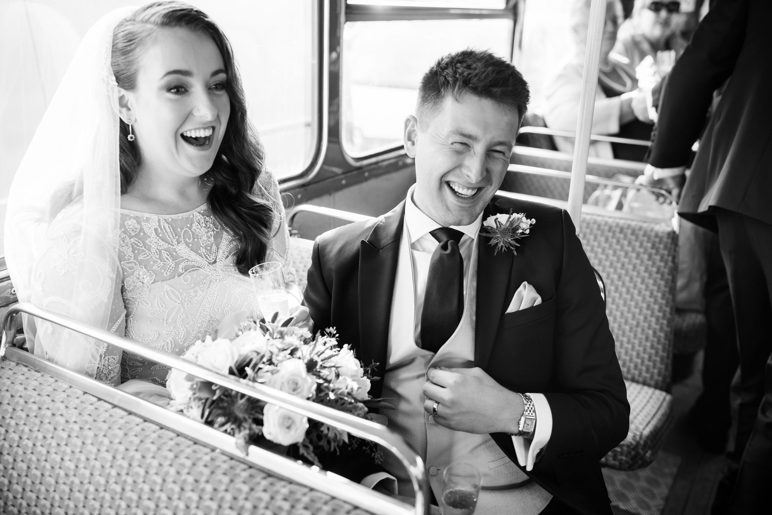 bride and groom laughing on routemaster London wedding