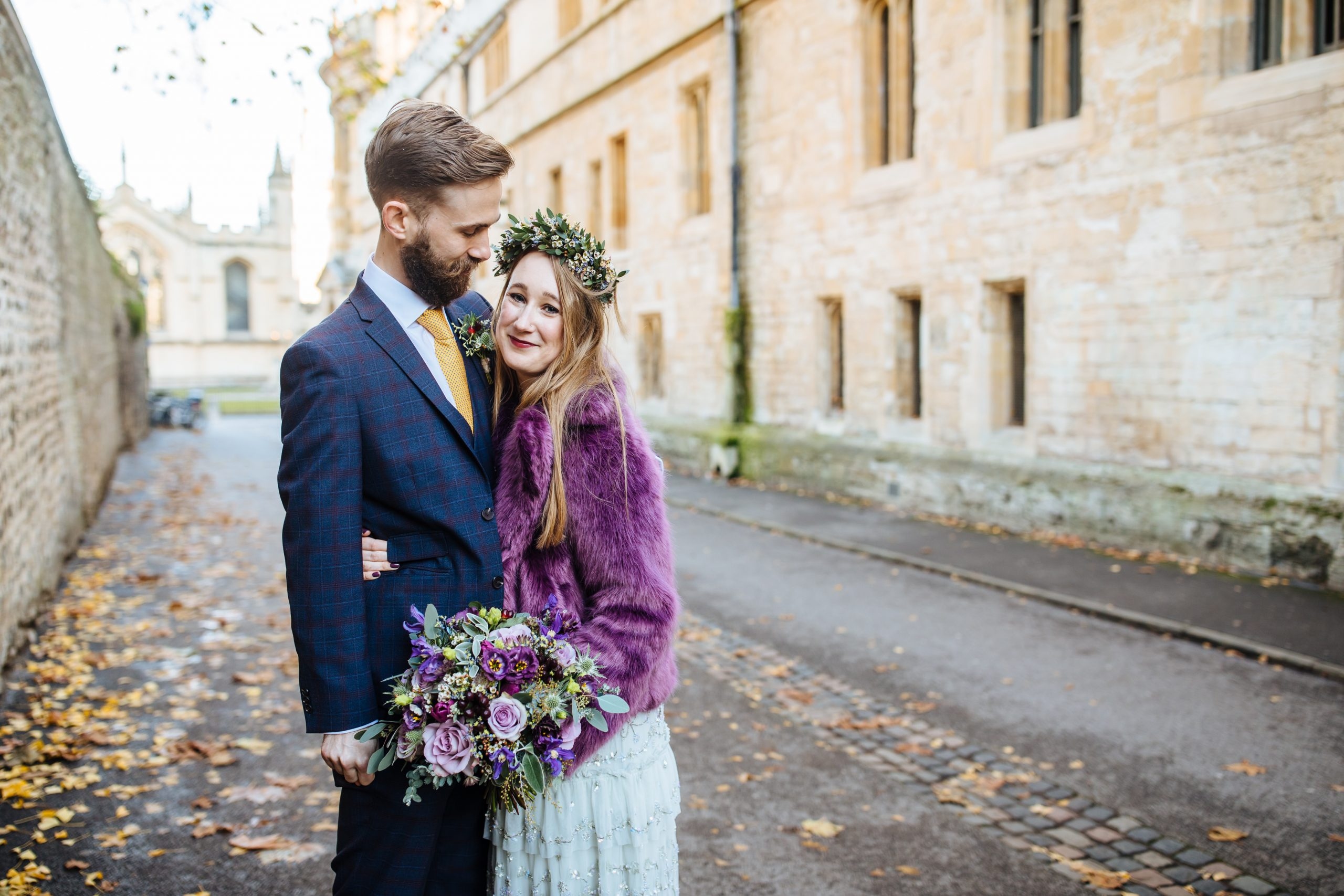 bride in needle and thread dress and purple coat hugging groom at Oxford wedding