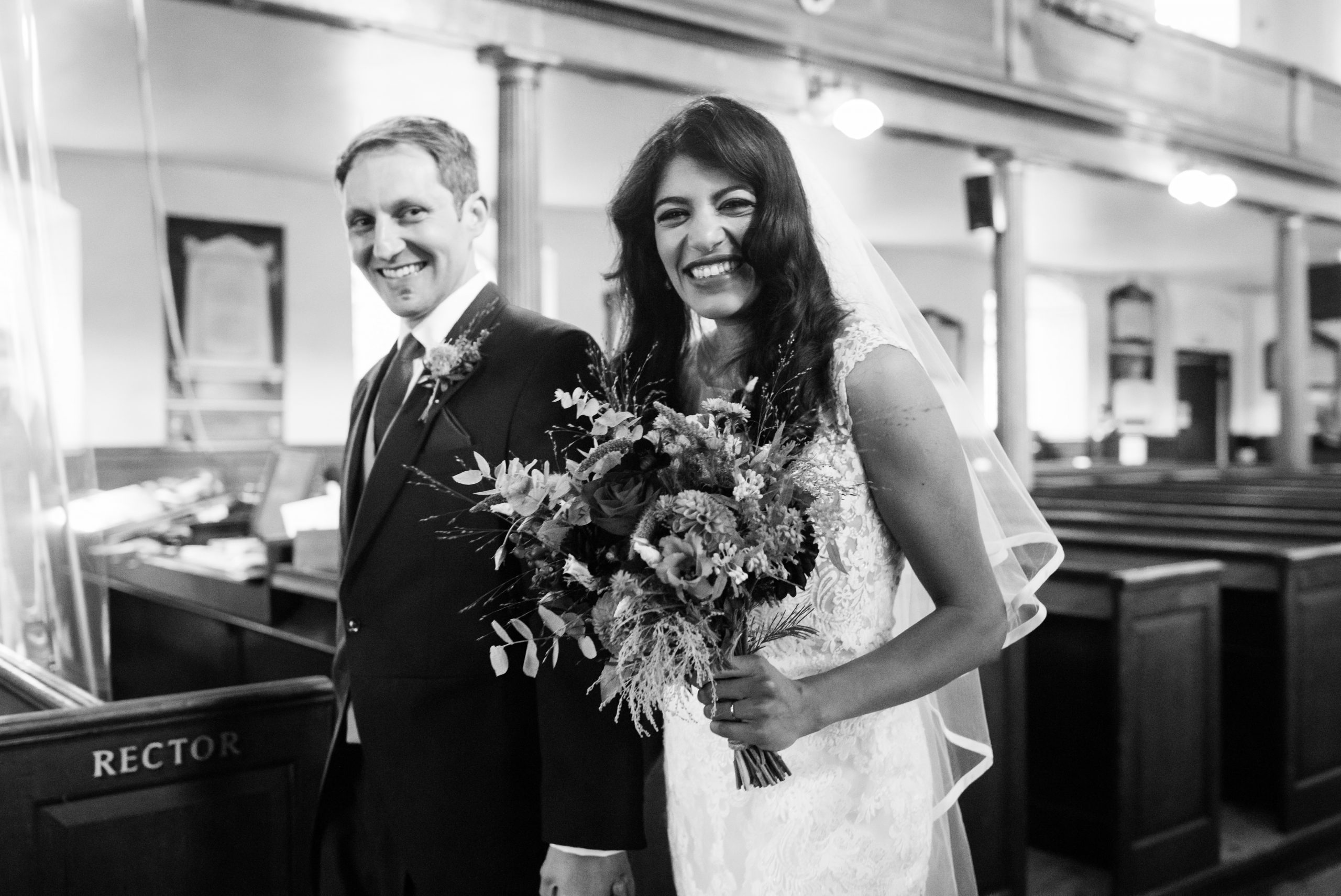 bride and groom smiling leaving the church