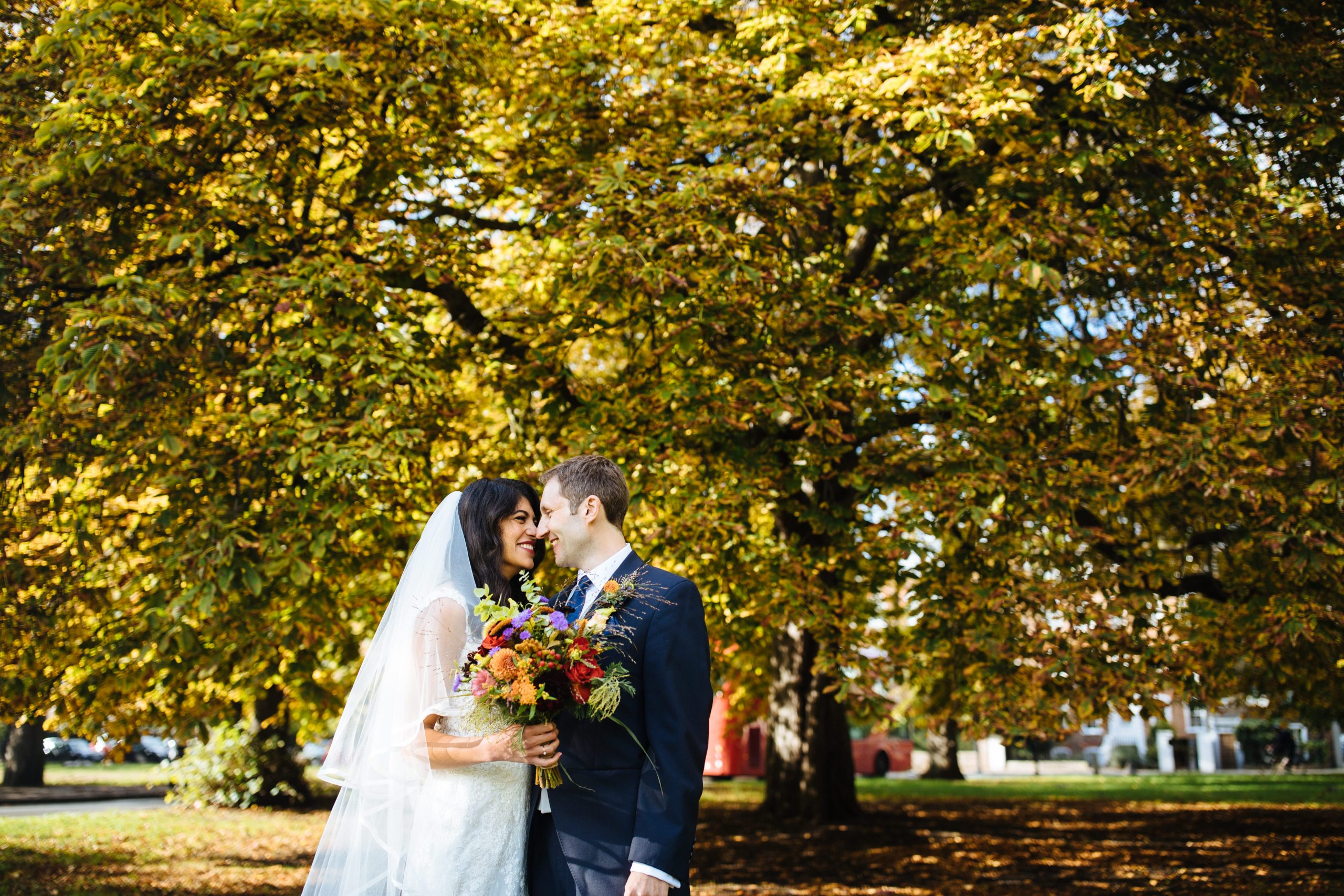 bride and groom cuddling in front of autumnal tree on Clapham Common