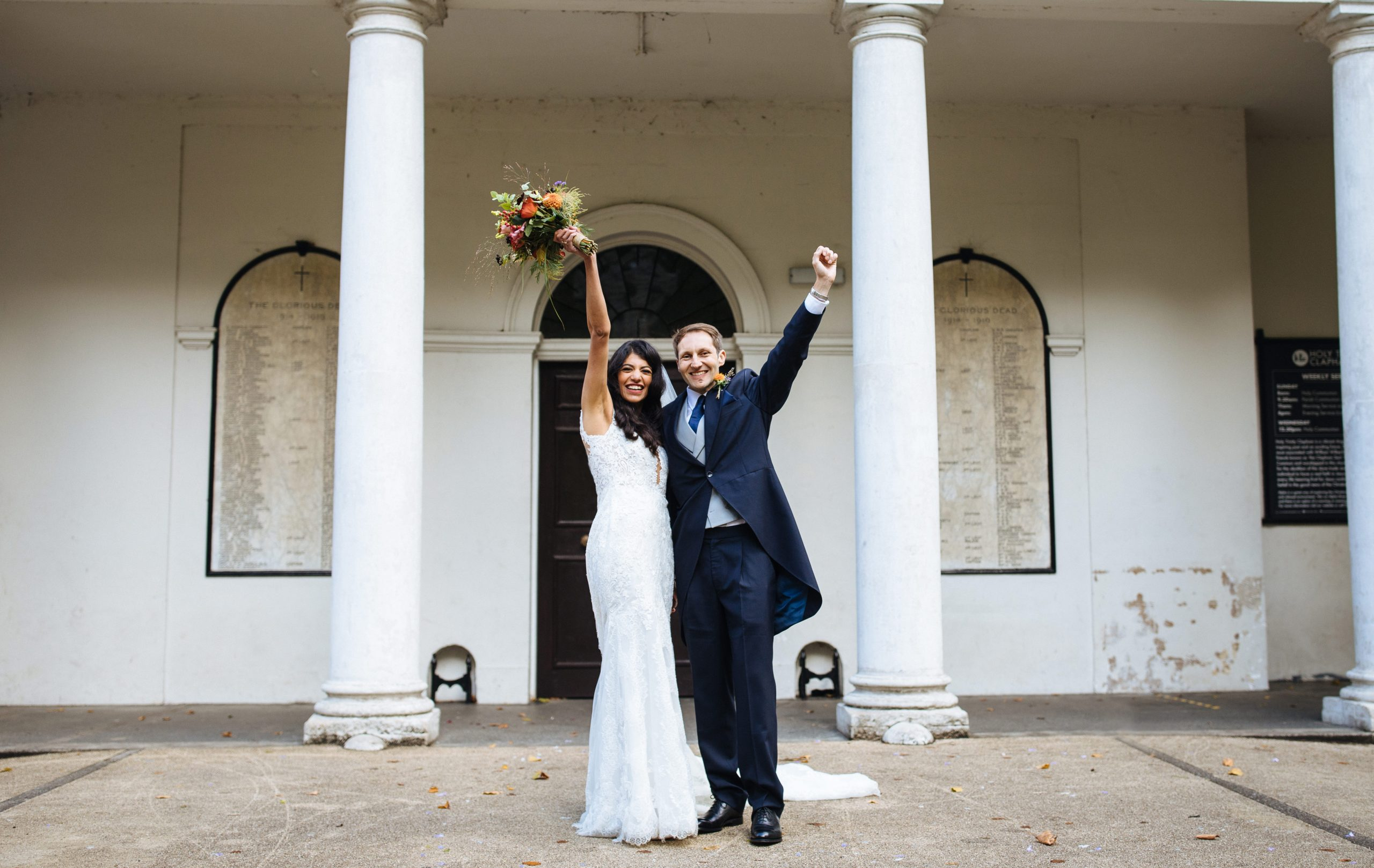 bride and groom punching the air in delight after wedding ceremony
