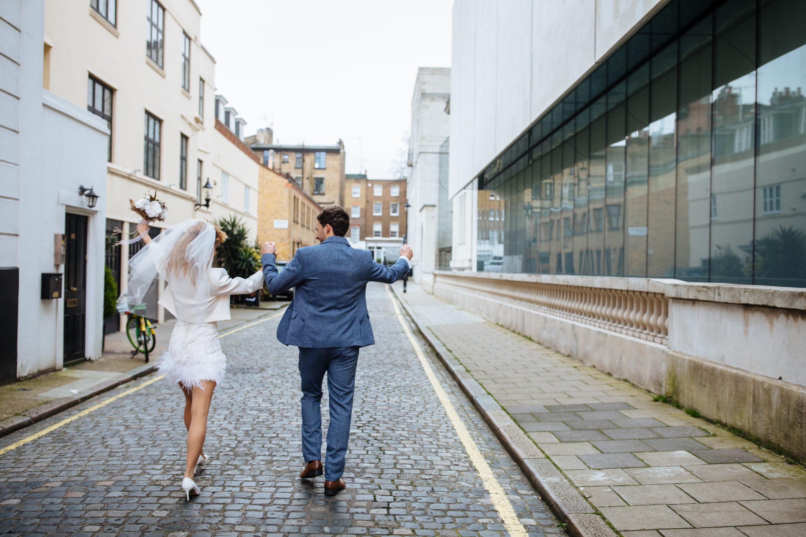 bride and groom walking and laughing at Marylebone town hall wedding