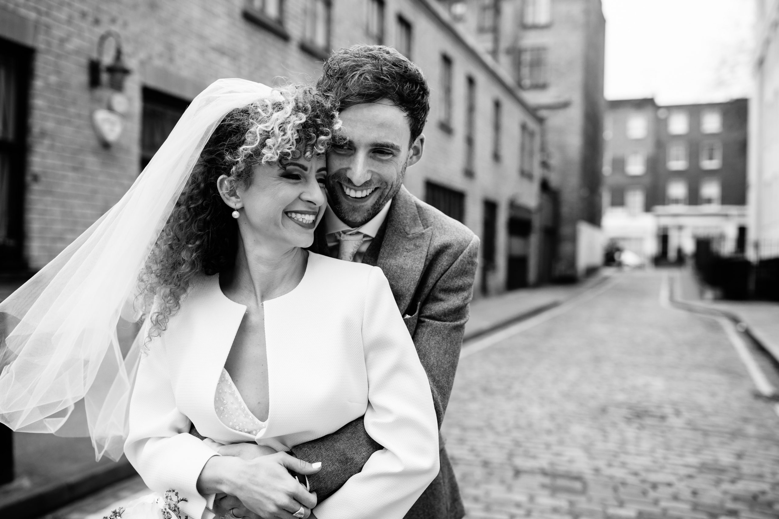 bride and groom hugging and laughing at wedding at Marylebone town hall